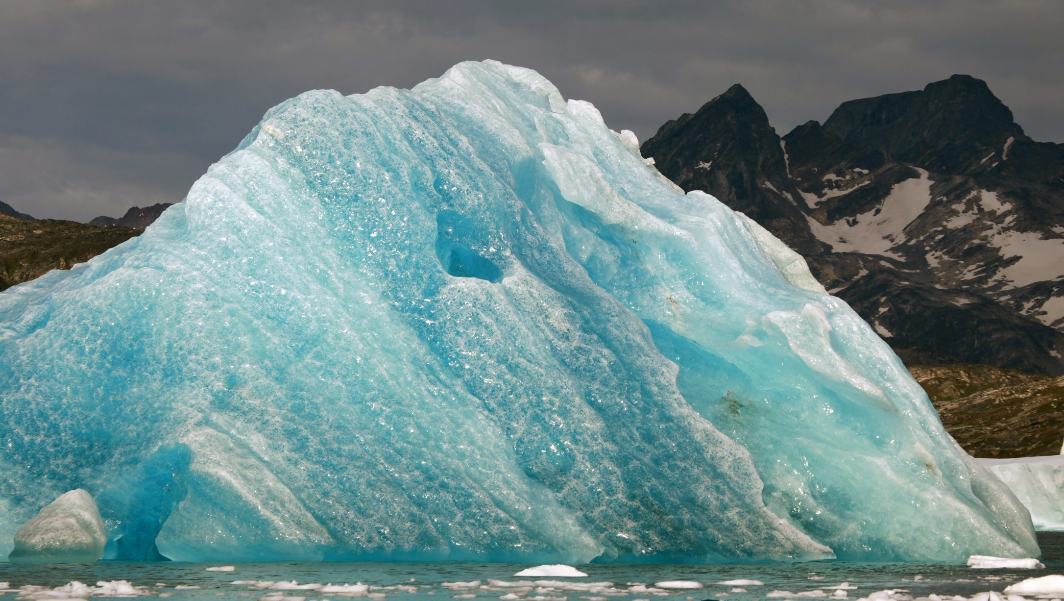 A deep blue iceberg floats in a fjord south of Tasiilaq in eastern Greenland August 2, 2009. The blue color is a result of compression and repeated thawing and refreezing. REUTERS/Bob Strong (GREENLAND) - RTR26KG7