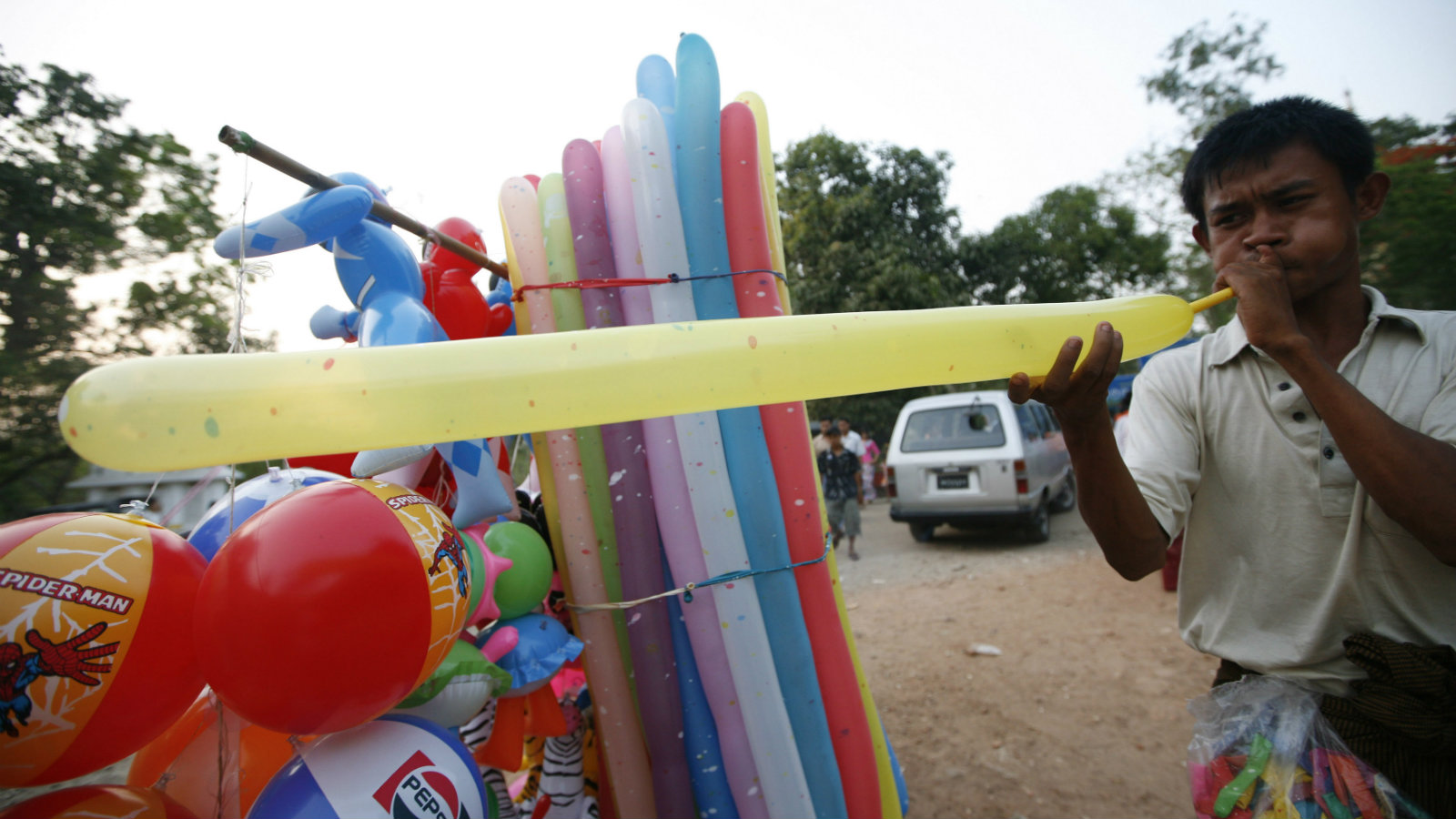 A balloon seller blows a balloon near Gabaraye Pagoda in Yangon April 17, 2010.