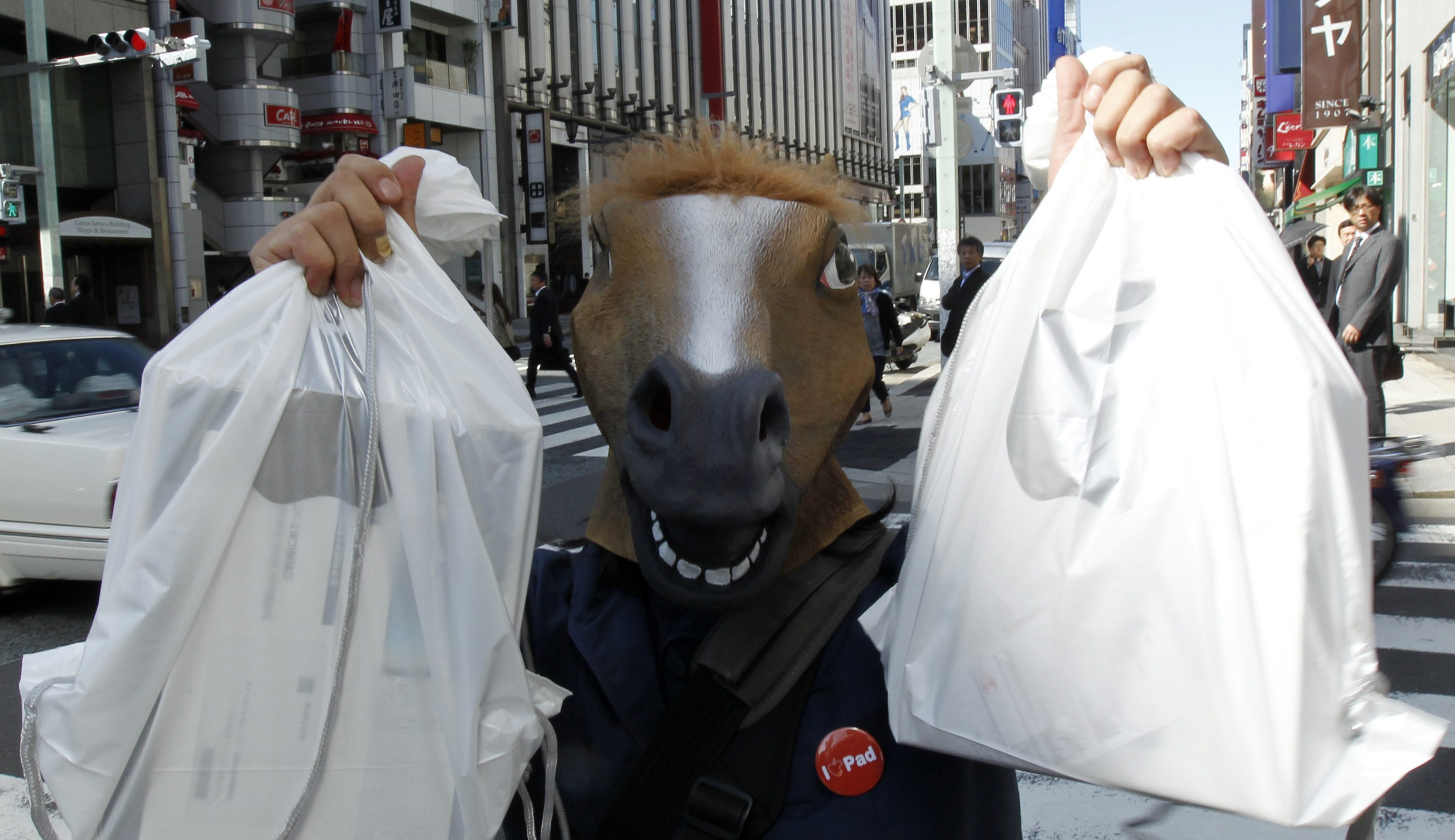 A man wearing a horse mask poses with his iPads after he bought them at an Apple store in Tokyo May 28, 2010.