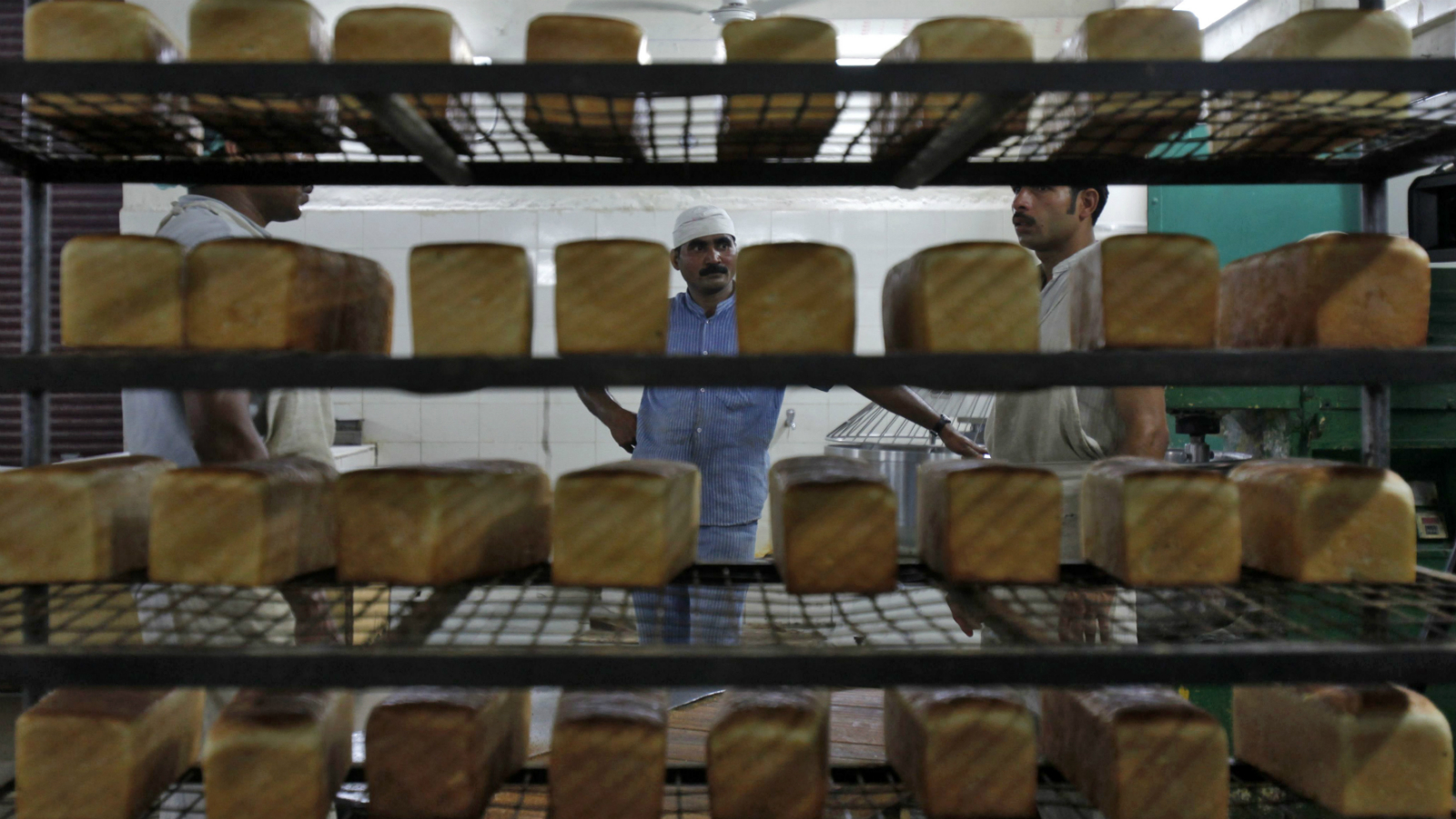 Inmates stand behind stacked bread at a bakery inside the Tihar Jail complex in New Delhi May 11, 2011. South Asia's largest prison - the Tihar Jail complex in New Delhi - is helping transform the lives of its inmates through vocational training in diverse fields to prepare them for a fresh start once they are released. A variety of goods ranging from crispy potato chips and crunchy cookies, to formal shirts, school desks, and herbal products are sold under the TJ'S (Tihar Jail) brand, to generate awareness about the positive activities happening inside the prison walls. Picture taken May 11, 2011.