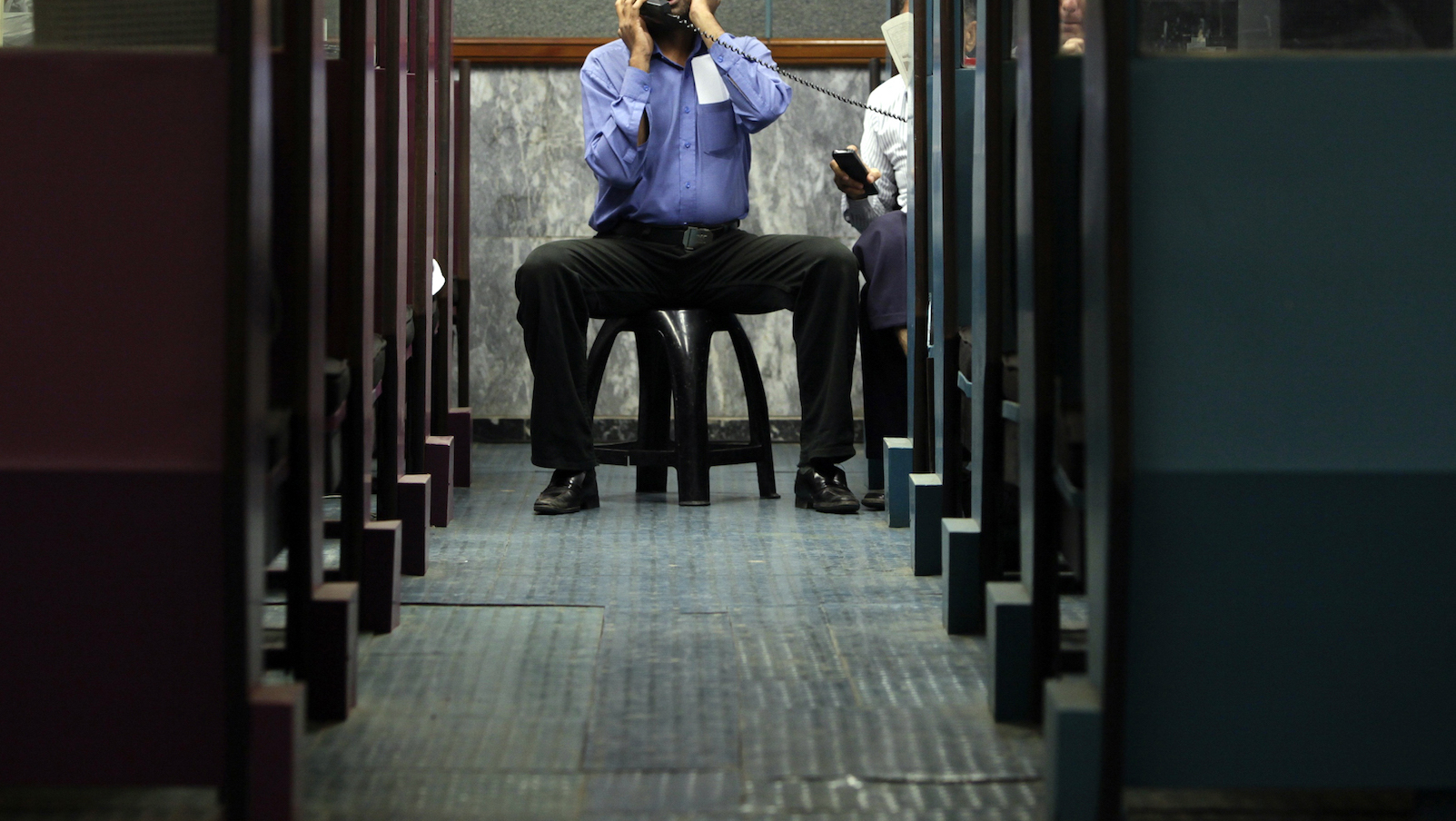 A man uses a phone between booths while monitoring share prices during a trading session at the Karachi Stock Exchange August 10, 2011. REUTERS/Akhtar Soomro (PAKISTAN - Tags: BUSINESS IMAGES OF THE DAY) - RTR2PSCA
