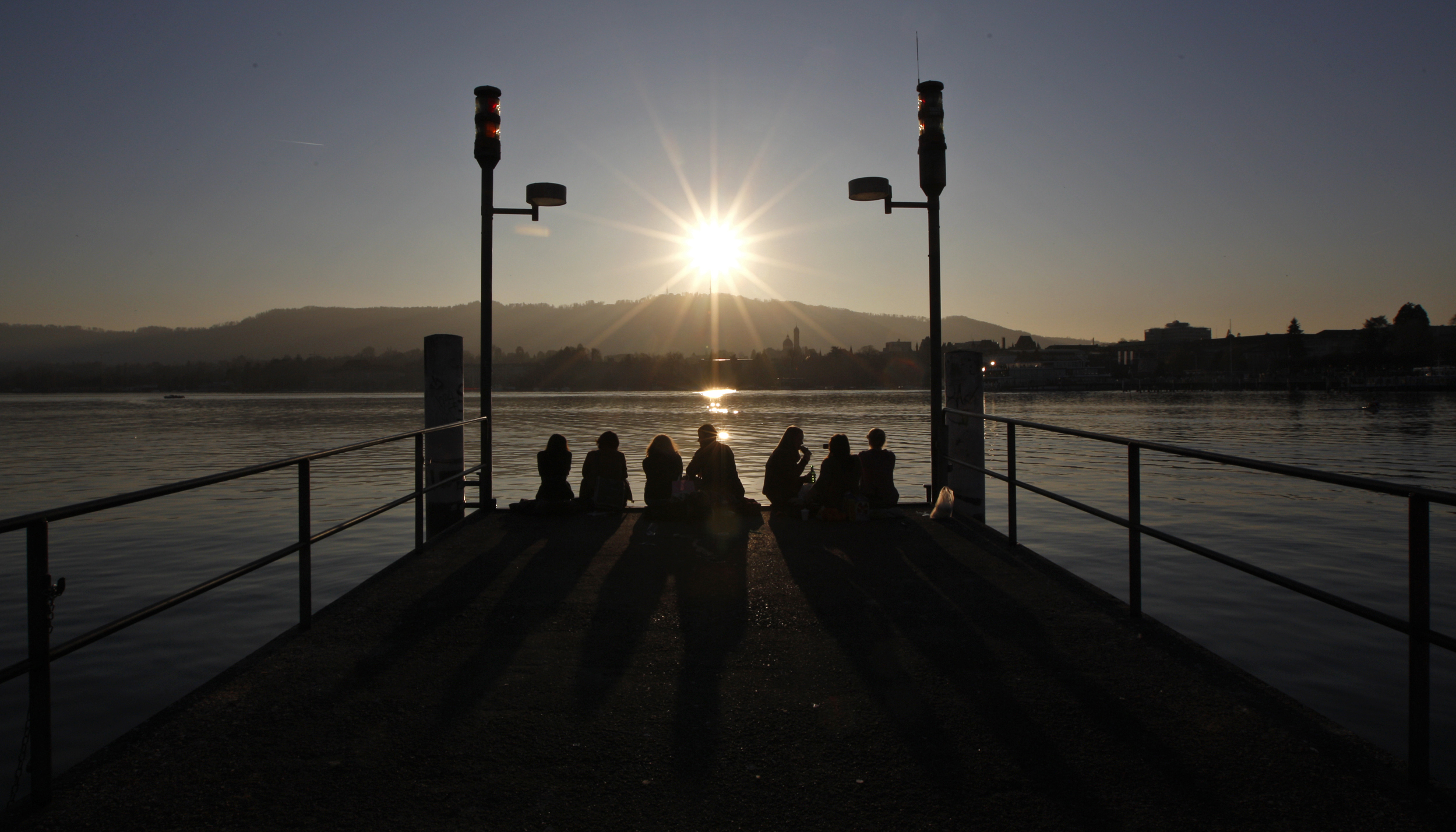 People on a pier are silhouetted as they enjoy a sunny and unusually mild afternoon on the edge of Lake Zurich, March 2, 2012. REUTERS/Christian Hartmann (SWITZERLAND - Tags: ENVIRONMENT SOCIETY) - RTR2YQVU