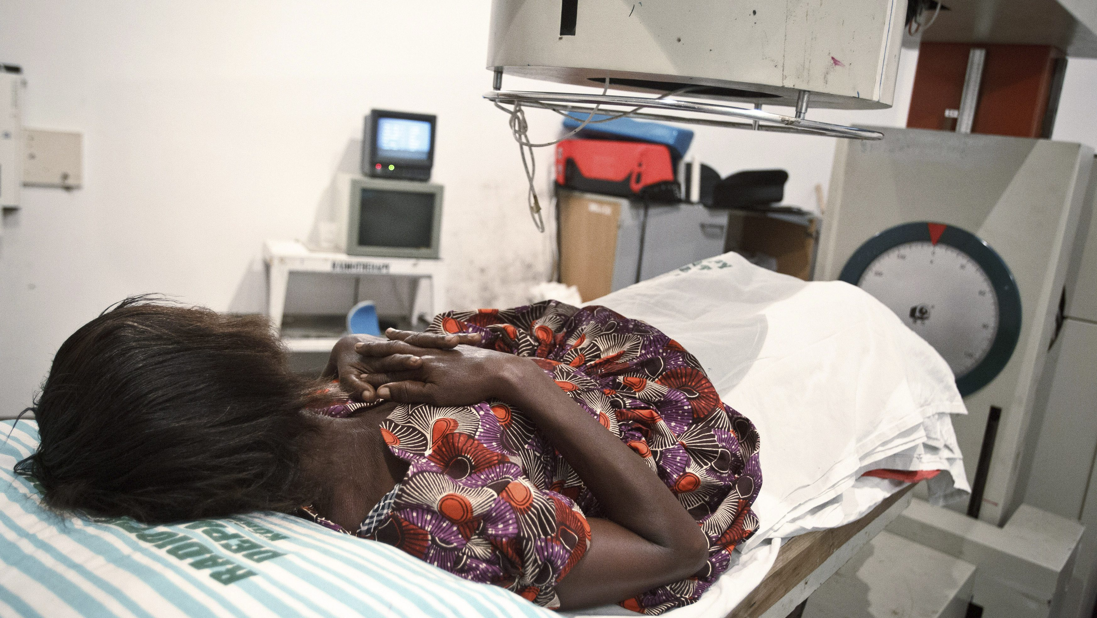 A 52-year-old woman suffering from bladder cancer lies under a radiotherapy simulator used to pinpoint areas to treat at the Korle Bu Teaching Hospital in Accra April 24, 2012. Most of Africa's around 2,000 languages have no word for cancer. The common perception in both developing and developed countries is that it's a disease of the wealthy world, where high-fat, processed-food diets, alcohol, smoking and sedentary lifestyles fuel tumour growth.   Yet there are an estimated one million new cancer cases sub-Saharan Africa will see this year - a number predicted to double to 2 million a year in the next decade.      Picture taken April 24, 2012. To match Insight CANCER-AFRICA/GHANA    REUTERS/Olivier Asselin (GHANA - Tags: HEALTH SOCIETY) - RTR31FSH