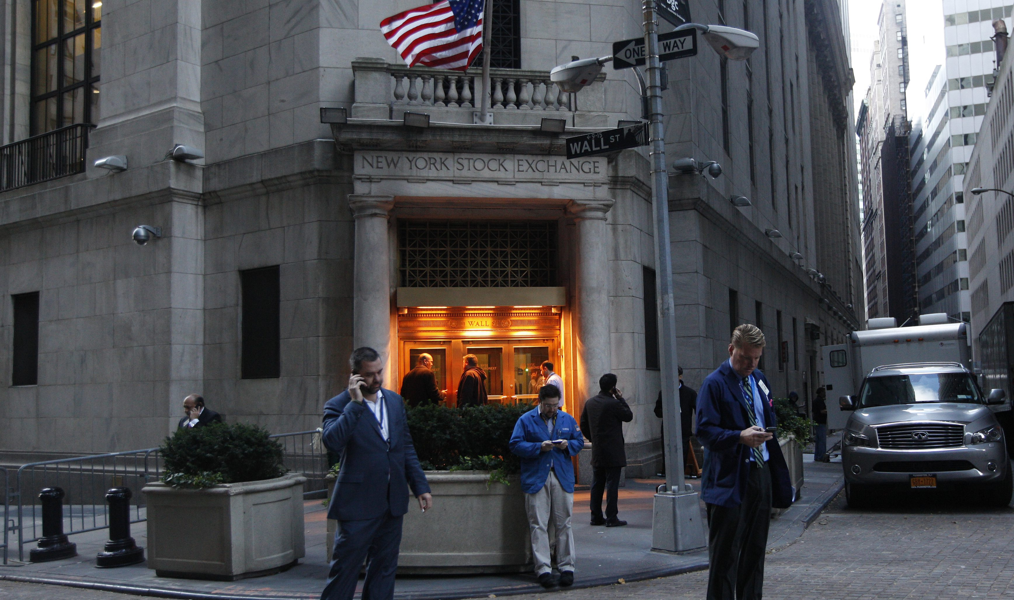 Traders stand outside the New York Stock Exchange prior to the opening bell