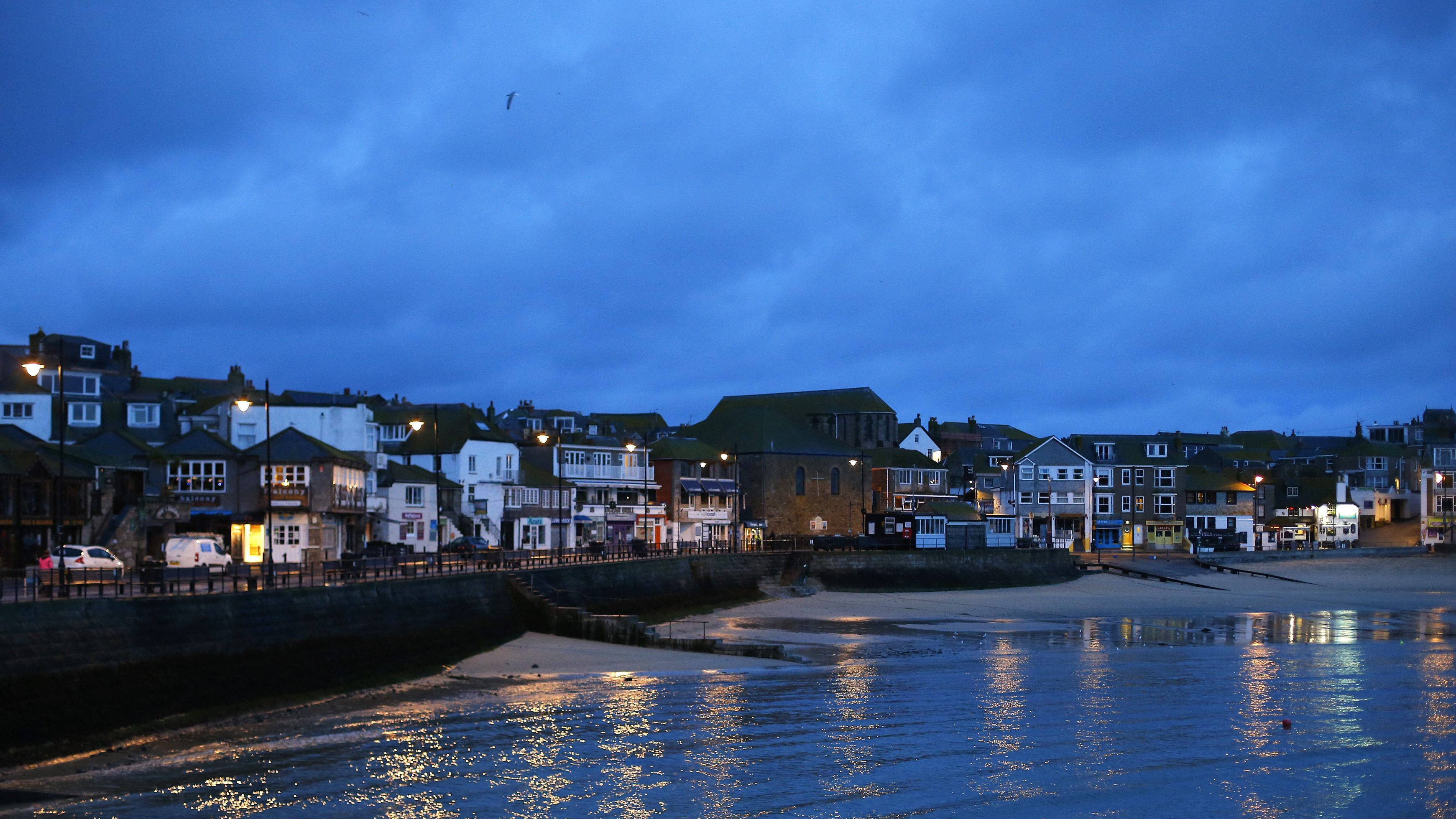 Lights are reflected in the harbour before dawn at St Ives in Cornwall