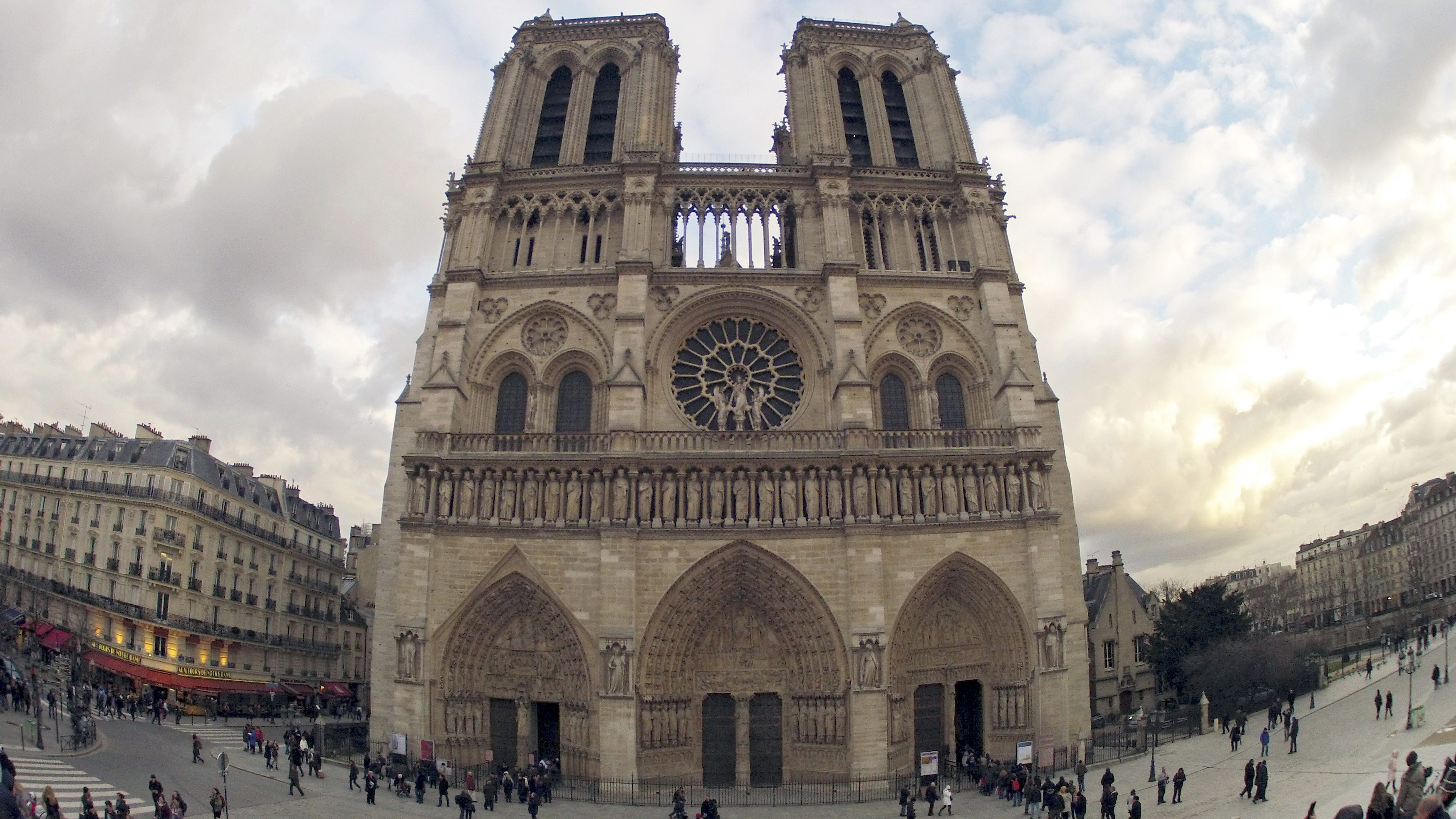 People walk past the entrance to the Notre Dame Cathedral in Paris February 8, 2013.