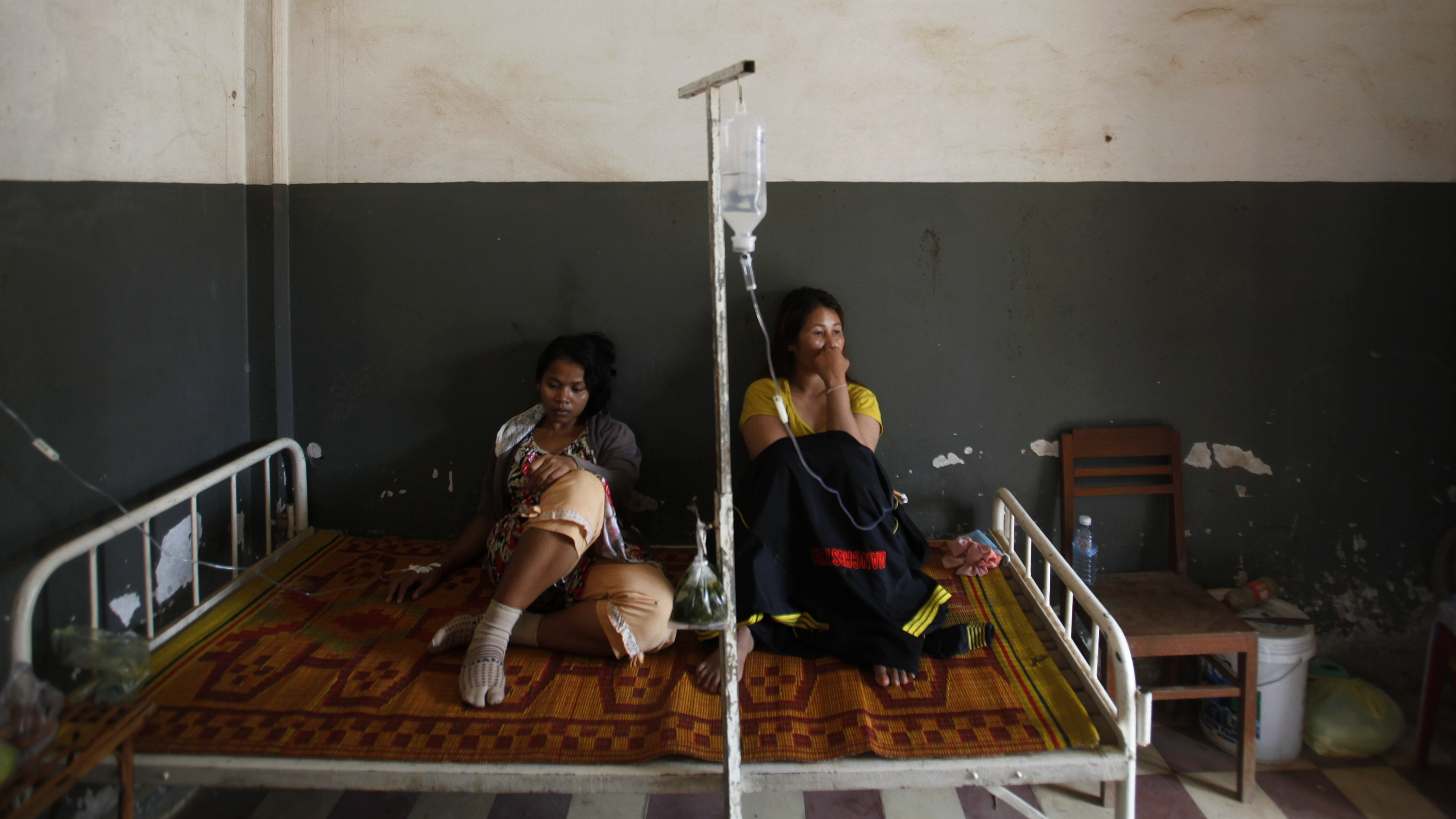 Garment workers from the Six Plus Industry Co. Ltd factory recover at a hospital after fainting at their workplace in Kandal province July 31, 2014. Around 200 workers from the factory producing clothing for Adidas collapsed at work on Thursday morning, said the Free Trade Union (FTU). Another 150 workers fainted on July 26 at the same factory, according to the union. REUTERS/Samrang Pring