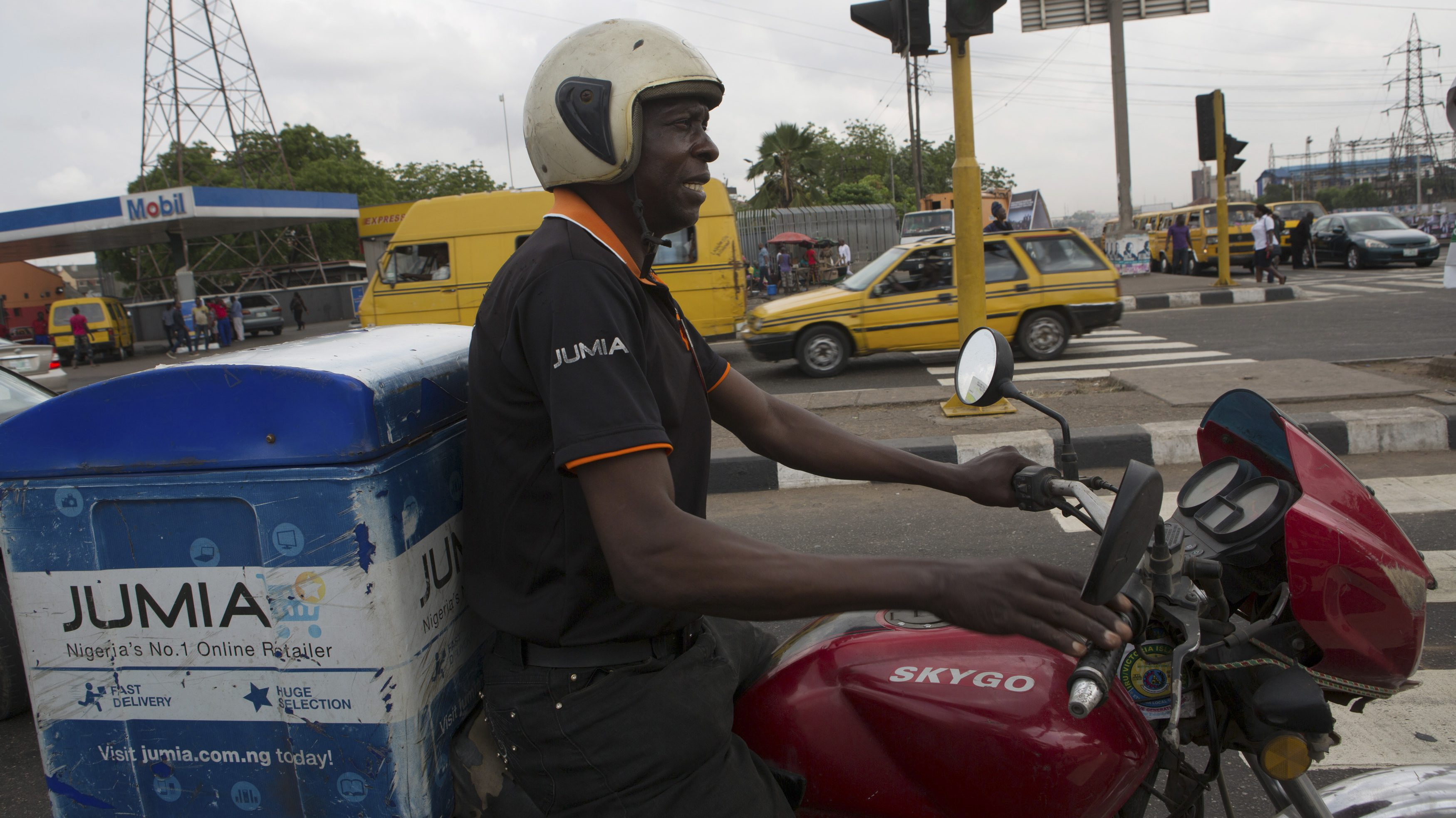 Moses Udoh, an employee of online retailer Jumia, makes a delivery by motorcycle in Lagos February 16, 2015. The growth of Africa's middle class has created demand for products that conventional retail struggles to satisfy due to a shortage of malls and grinding traffic in many cities that deters shoppers. The sector is still in its infancy. The internet's contribution to Africa's gross domestic product stood at 1.1 percent in 2013, much lower than other emerging markets. But this could rise to 10 percent, or $300 billion, by 2025, according to a report by consultants McKinsey's & Company. REUTERS/Joe Penney (NIGERIA - Tags: BUSINESS TRANSPORT SOCIETY EMPLOYMENT) - RTR4PT4B