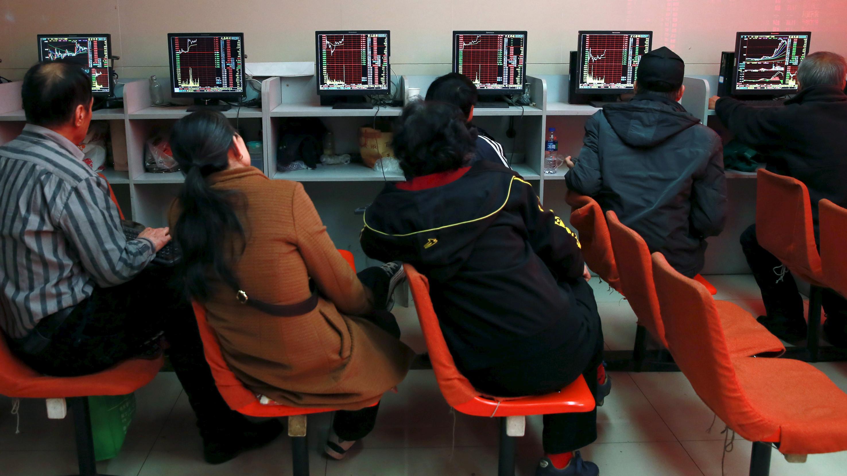 Investors look at computer screens showing stock information at a brokerage house in Shenyang, Liaoning province, April 13, 2015.
