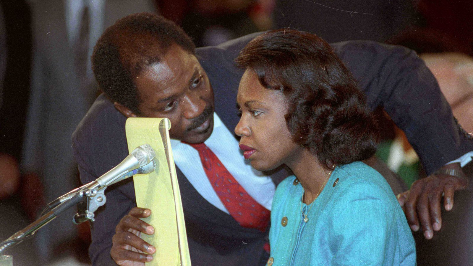 Counsel Charles Ogeltree uses a legal pad to cover a microphone as he advises law professor Anita Hill during her testimony October 11, 1991 before the Senate Judiciary Committee hearings on Supreme Court nominee Judge Clarence Thomas. Hill testified she was sexually harassed by Thomas while she was his aide; Thomas has denied the charges.
