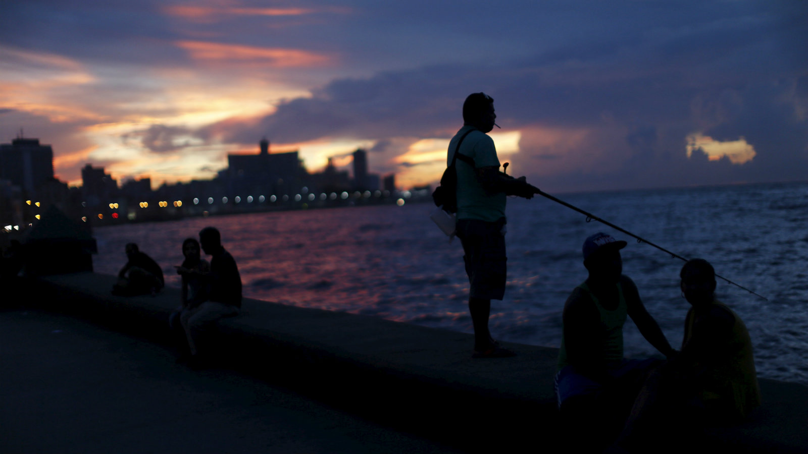 A resident fishes as others hang out at the Malecon seafront in Havana September 18, 2015. The Obama administration announced wide-ranging new rules on Friday to ease trade, travel and investment restrictions with Cuba, the latest effort to chip away at the long-standing U.S. economic embargo amid a diplomatic thaw between the two former Cold War foes. The announcement came just as Pope Francis, who played an instrumental role in the diplomatic opening late last year, prepares to visit Cuba this weekend before heading to the United States next week. The Vatican has long condemned the embargo against Cuba.