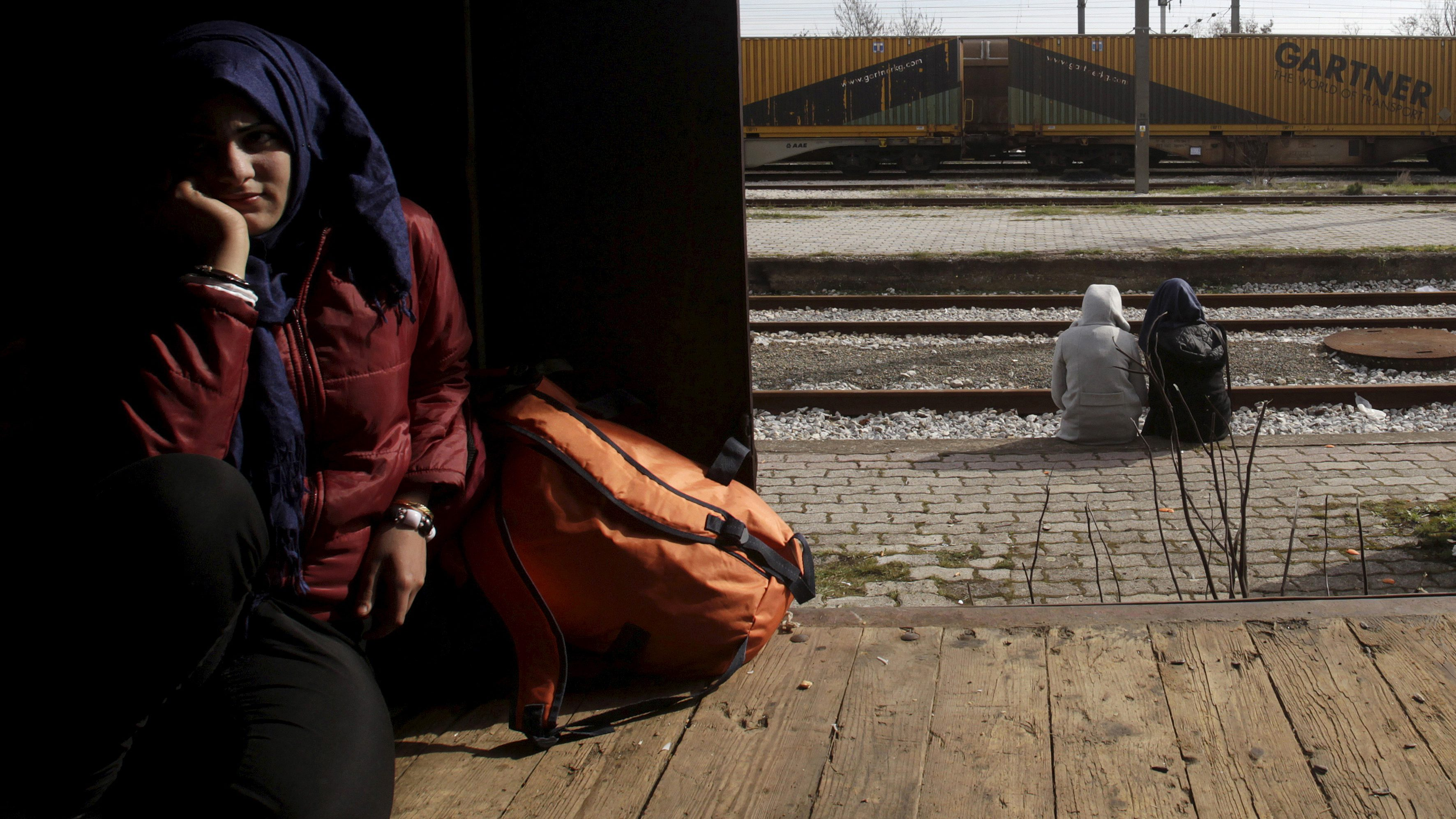 A migrant (L) finds shelter in a train wagon as others sit near the railway tracks at the Greek-Macedonian border, near the village of Idomeni, Greece March 6, 2016. REUTERS/Alexandros Avramidis      TPX IMAGES OF THE DAY      - RTS9IP6