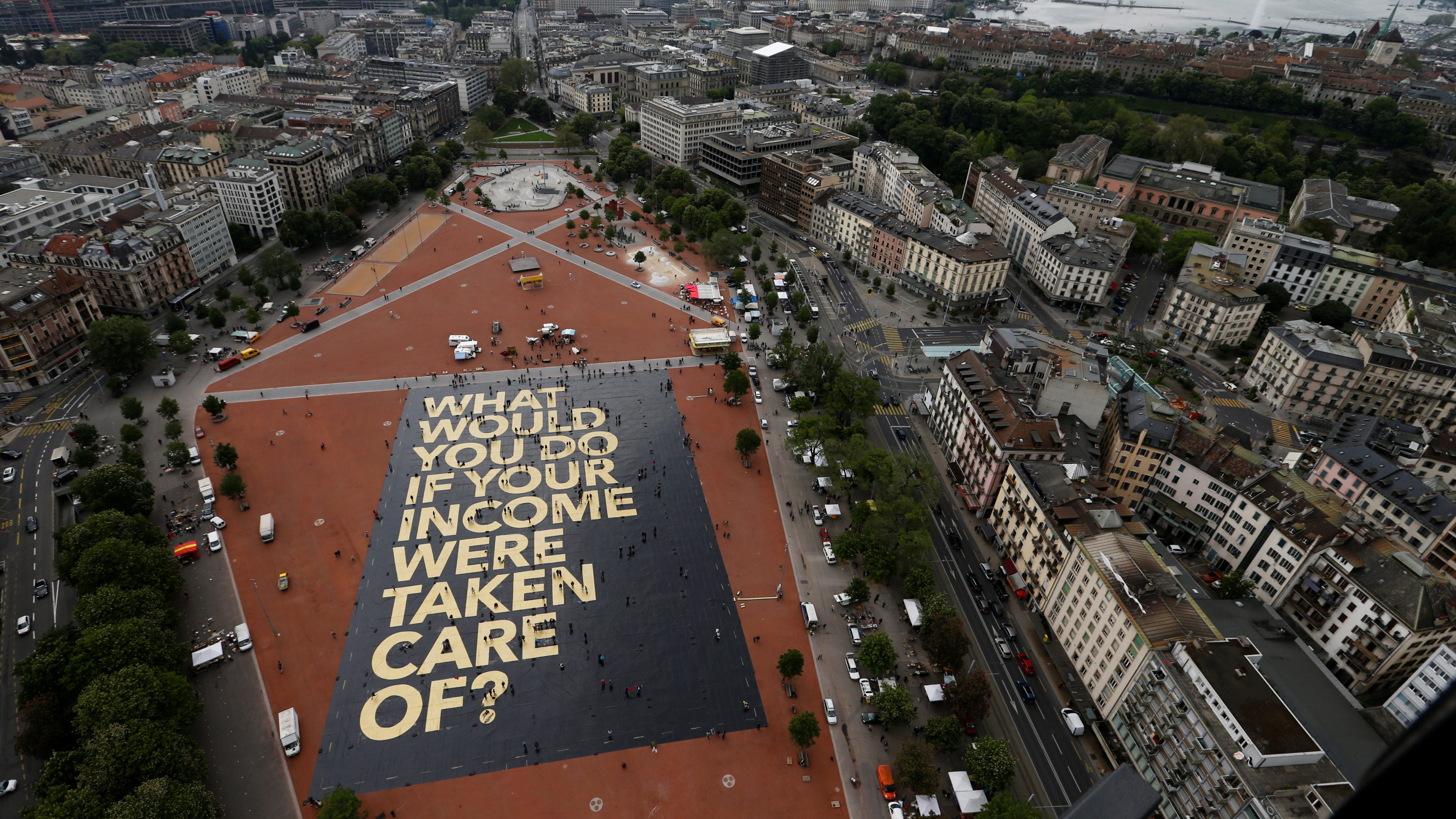 """A 8,000 square meter poster is pictured on the Plainpalais square in Geneva, Switzerland May 14, 2016. The committee for the initiative for an """"Unconditional Basic Income"""" has crowdfunded the """"world's biggest poster"""", posing the question """"What would you do if your income were taken care of ?"""". Swiss citizens will vote on June 5, 2016 on the proposal for an """"Unconditional Basic Income"""". REUTERS/Denis Balibouse TPX IMAGES OF THE DAY - RTSEA8F"""