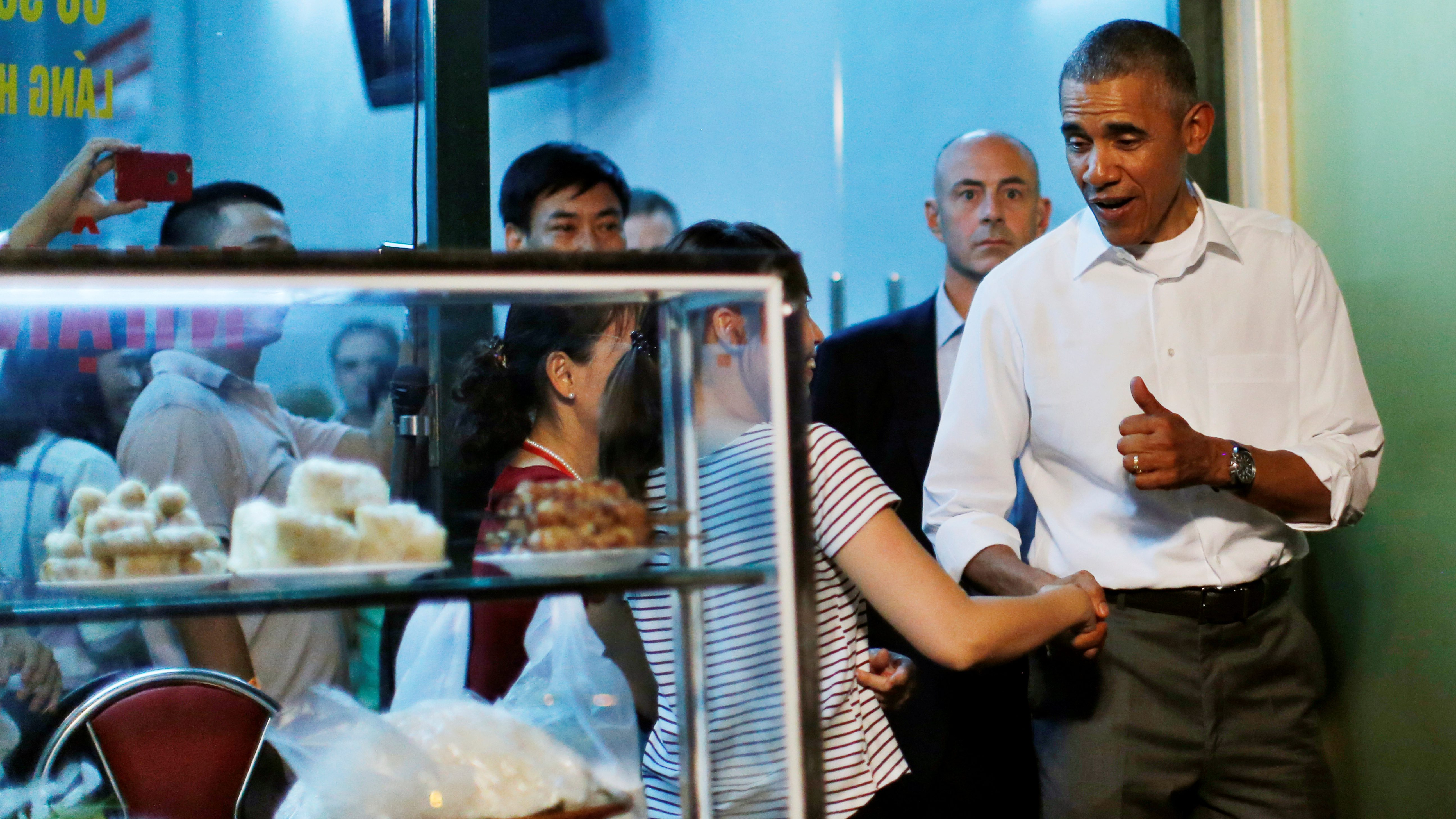 U.S. President Barack Obama shakes hands with a local resident as he leaves after having a dinner with Anthony Bourdain at the restaurant in Hanoi, Vietnam May 23, 2016. REUTERS/Carlos Barria TPX IMAGES OF THE DAY      - RTSFJST