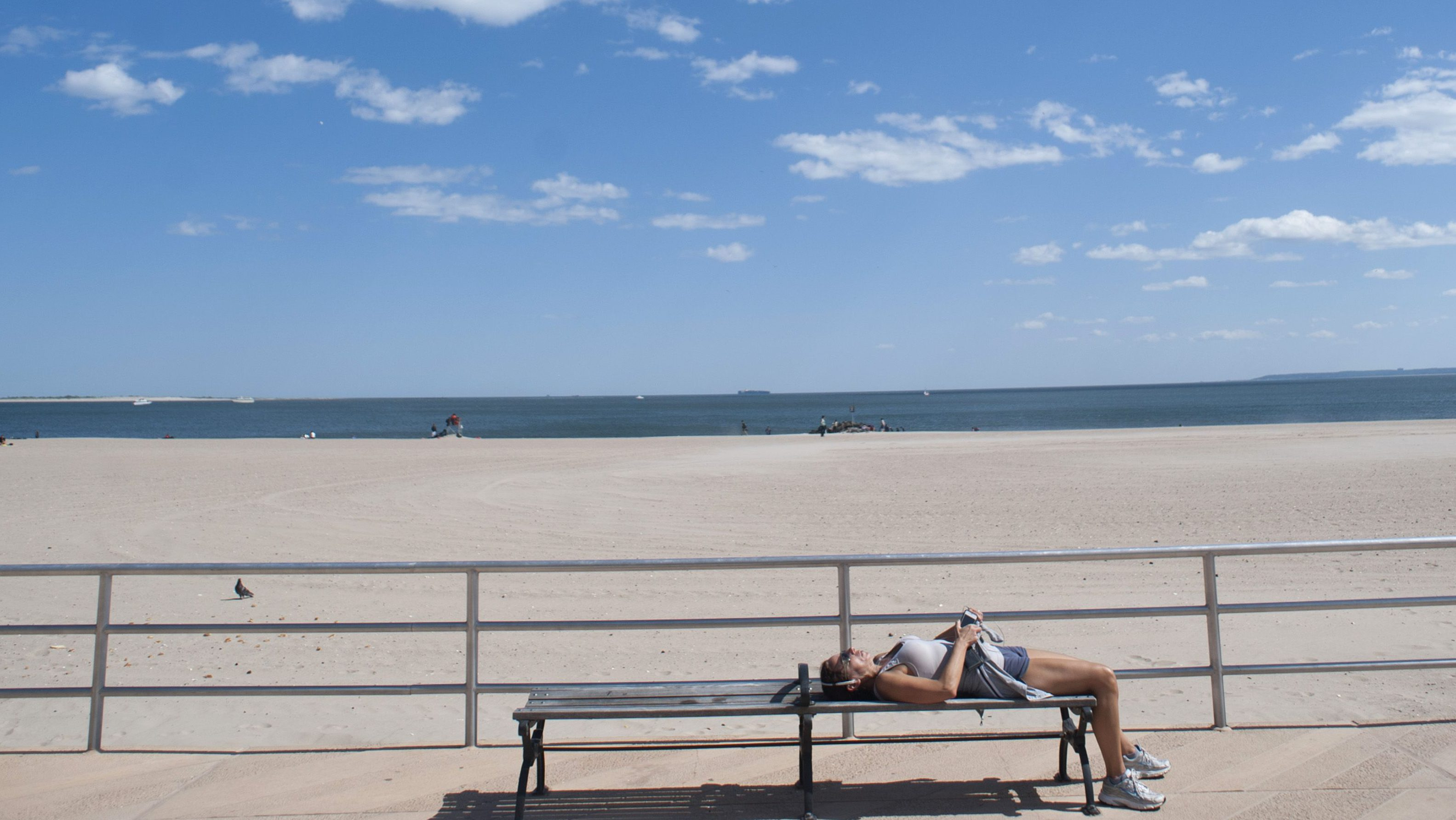 A woman lays on a bench along the boardwalk in Coney Island in the Brooklyn Borough of New York, May 26, 2013. Seven months after Hurricane Sandy, New York's beaches have reopened before the Memorial Day holiday.   (UNITED STATES - Tags: ENVIRONMENT SOCIETY) - RTX102C1