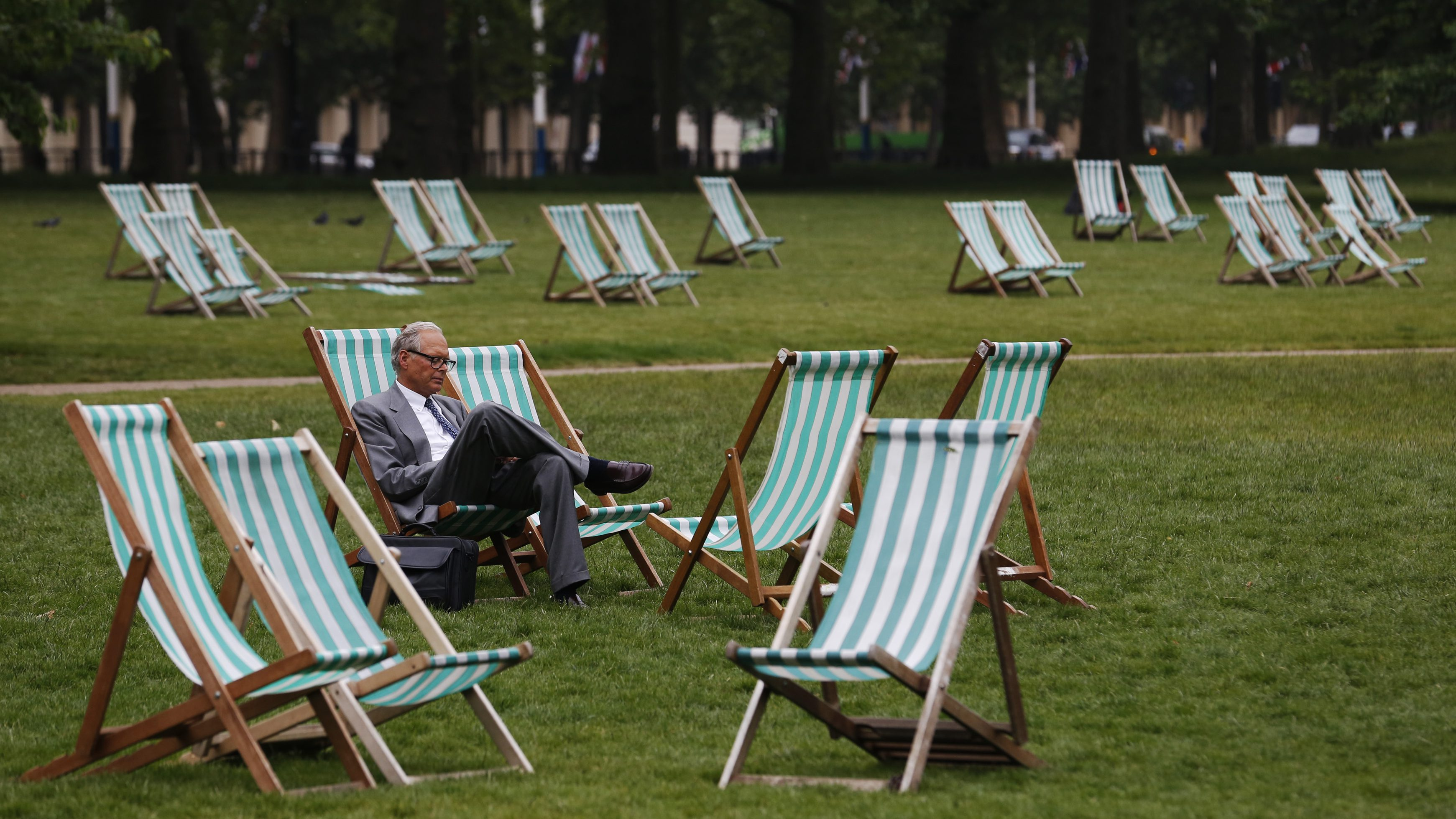 A man sits among empty deck chairs during the unseasonably poor summer weather, in St James's Park in London June 18, 2013. REUTERS/Luke MacGregor (BRITAIN - Tags: ENVIRONMENT SOCIETY TRAVEL) - RTX10S6X