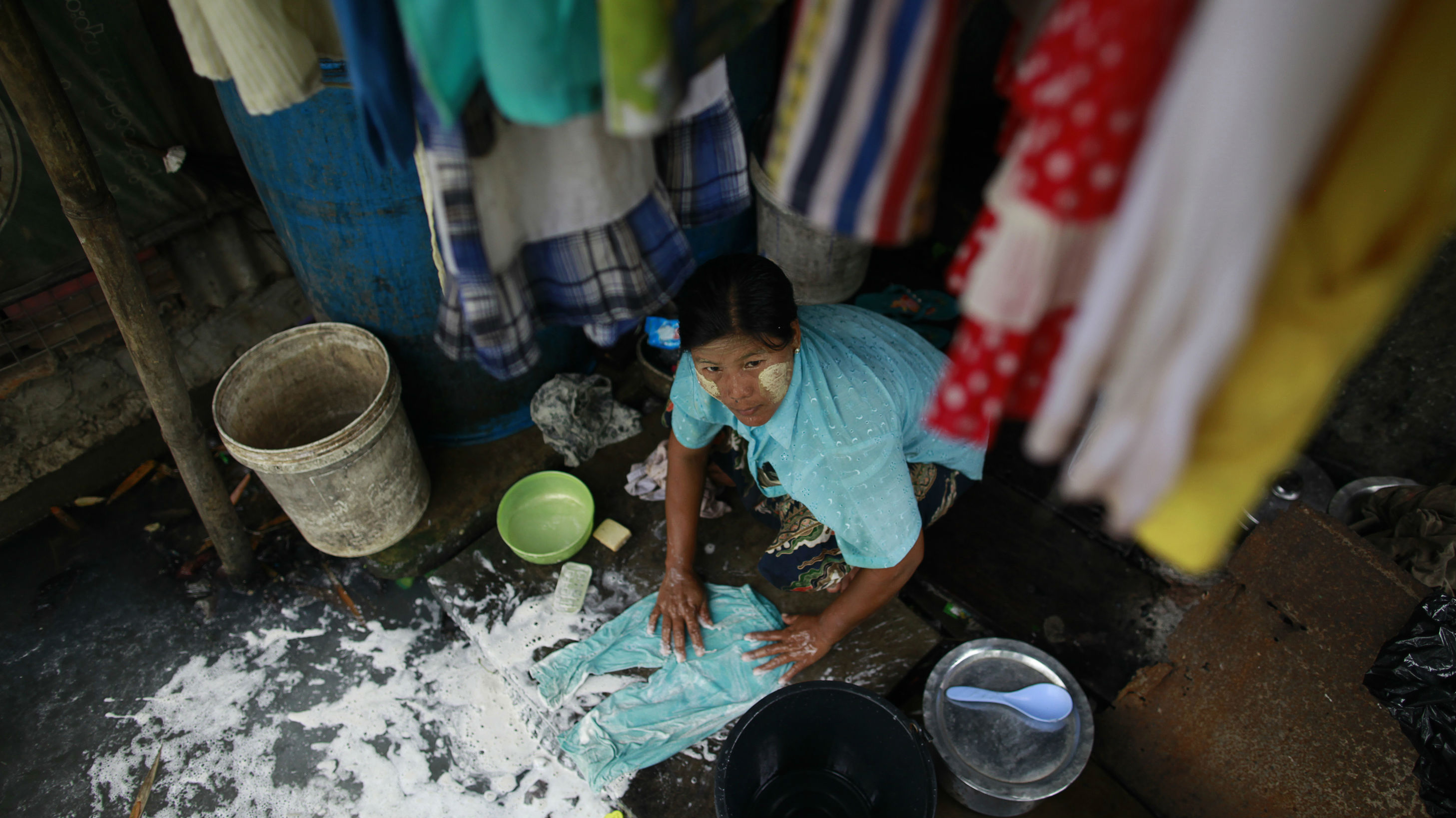 A woman washes clothes in her home at a slum area in Yangon June 25, 2013