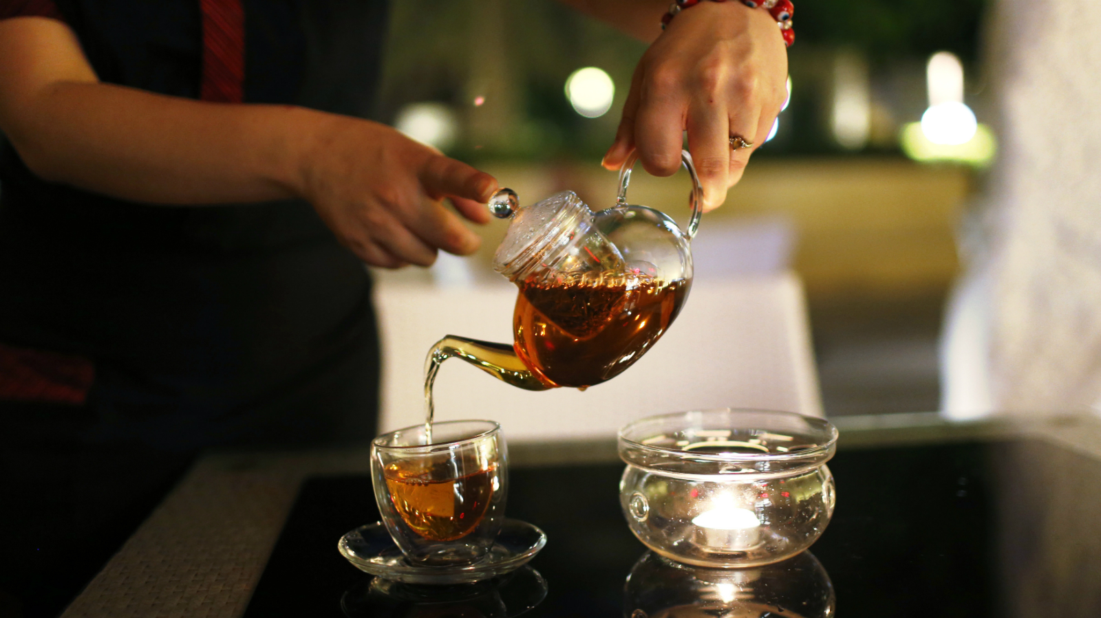 A server pours a pot of tea, made from gold-plated tea leaves, for customers at Mocca art cafe in Dubai September 21, 2013. The cafe is the first to serve such tea in the Middle East. The tea was sourced from Ceylon, sent to Germany for gold plating and then to Morocco for flavouring.