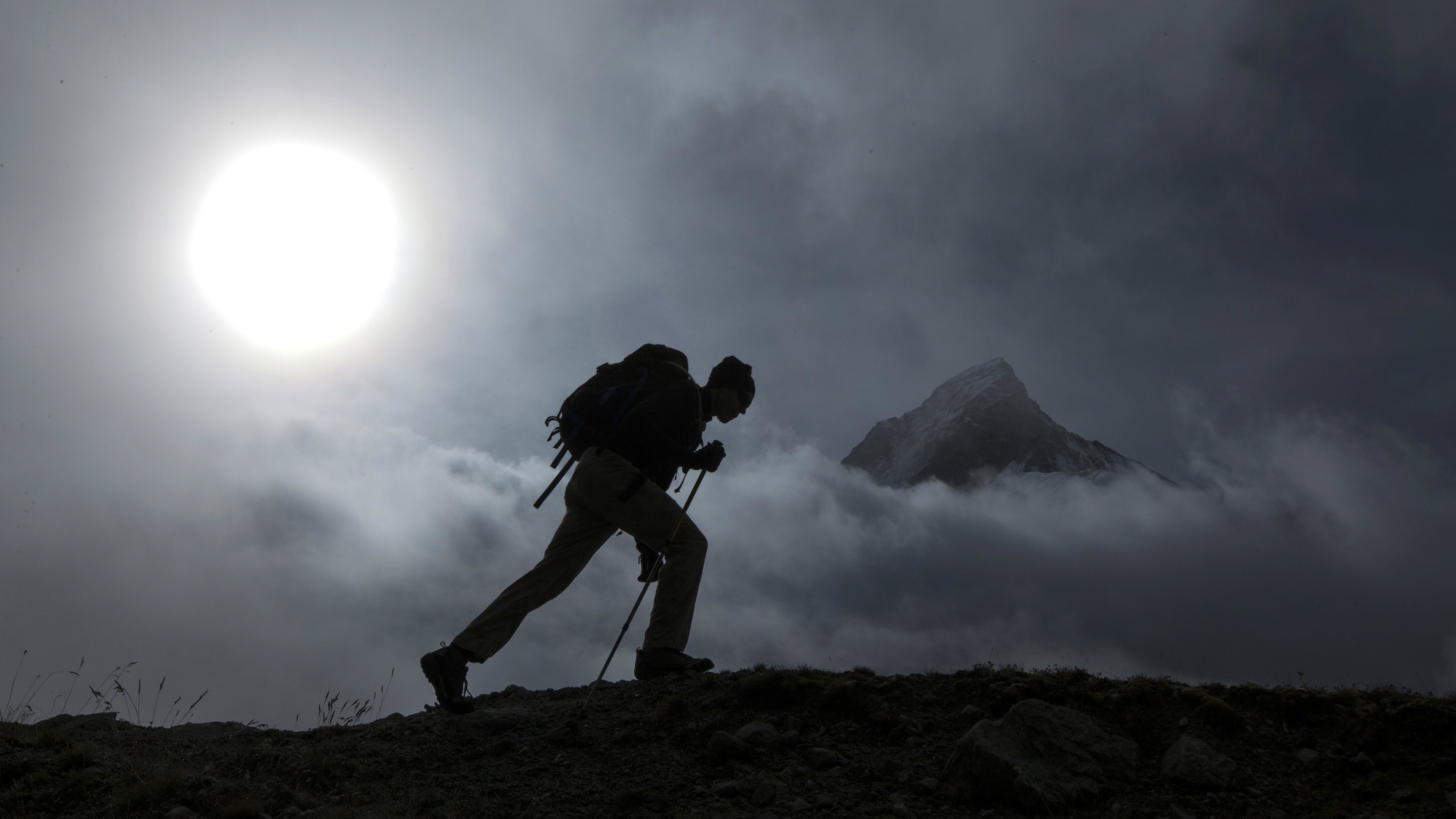 A hiker walks past the Matterhorn mountain at sunrise in the Swiss Alps near Zermatt September 11, 2013. Picture taken September 11, 2013.