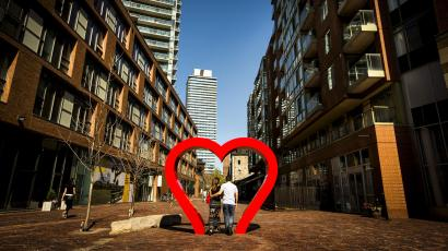 A young couple walks through a heart shaped installation in the Distillery District in Toronto.