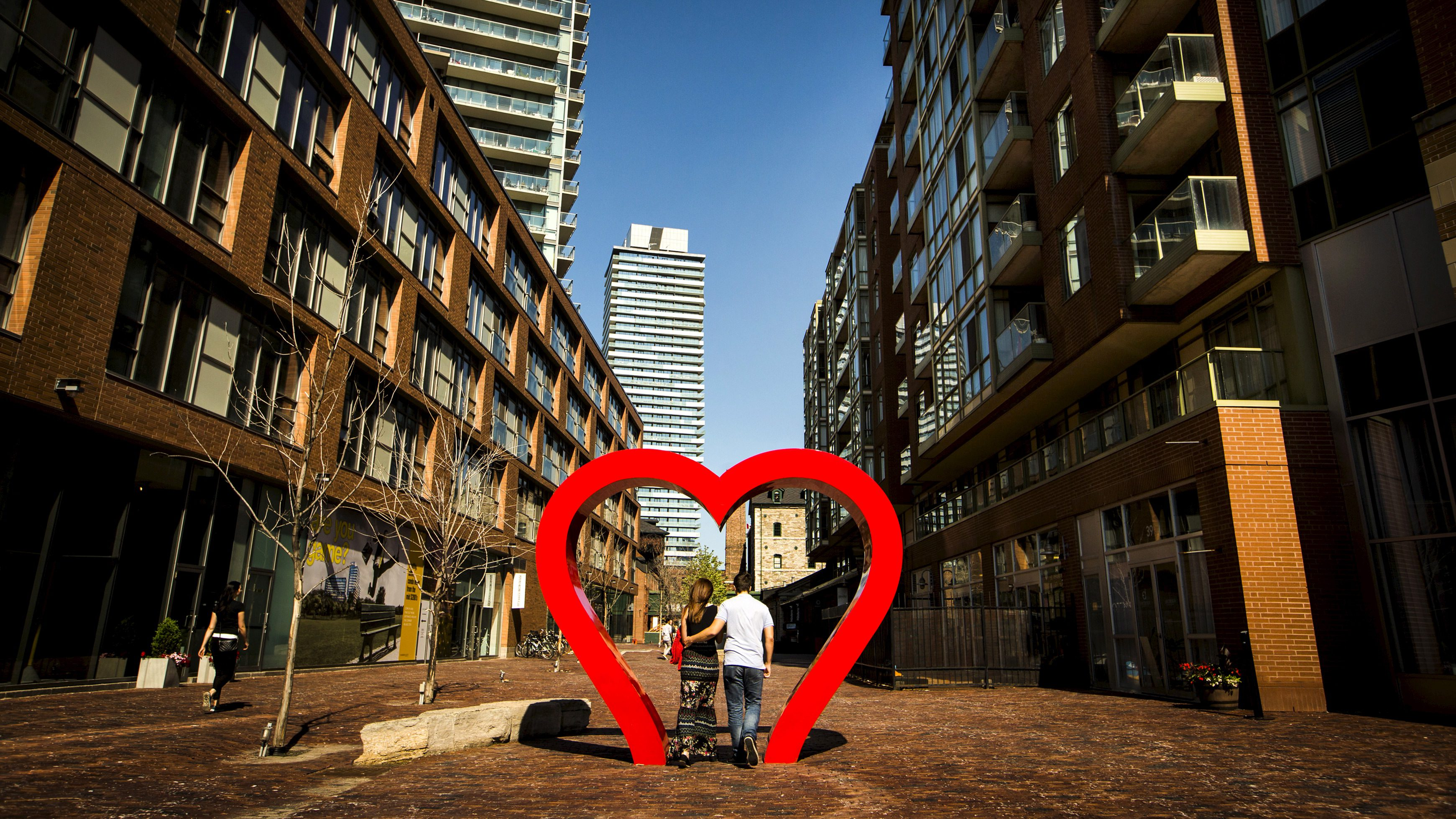 A young couple walks through a heart shaped installation in the Distillery District in Toronto, June 16, 2015.