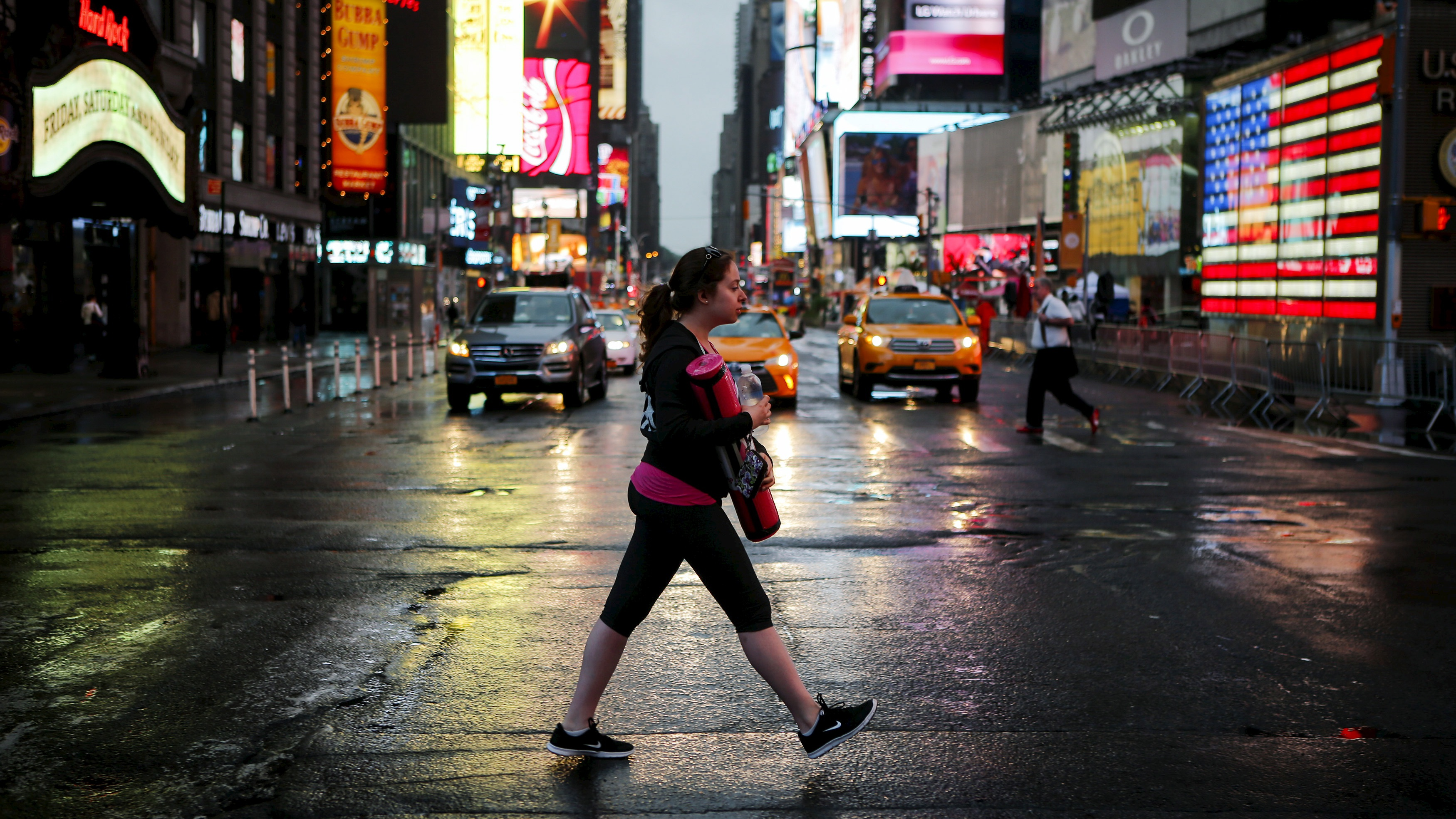 A woman arrives to practice yoga in Times Square as part of a Summer Solstice and International Day of Yoga celebration in New York June 21, 2015.