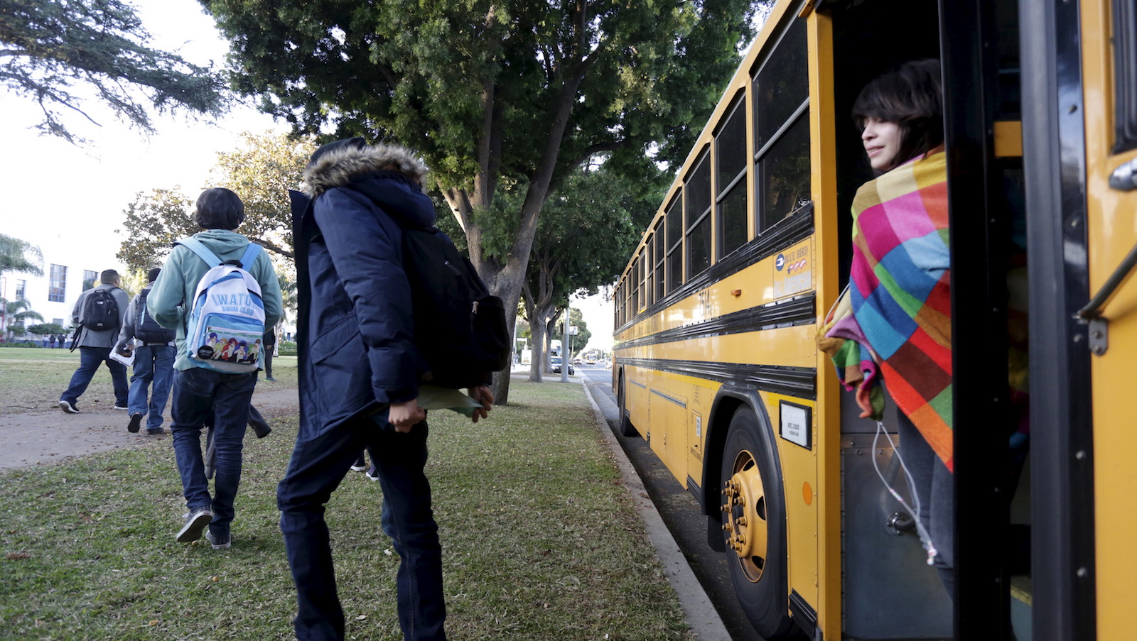 Students exit a bus as they arrive at Venice High School in Los Angeles, California December 16, 2015. Classes resume today in Los Angeles, the second largest school district in the United States,  after they were closed on Tuesday after officials reported receiving an unspecified threat to the district and ordered a search of all schools in the city. REUTERS/Jonathan Alcorn - RTX1YZF0