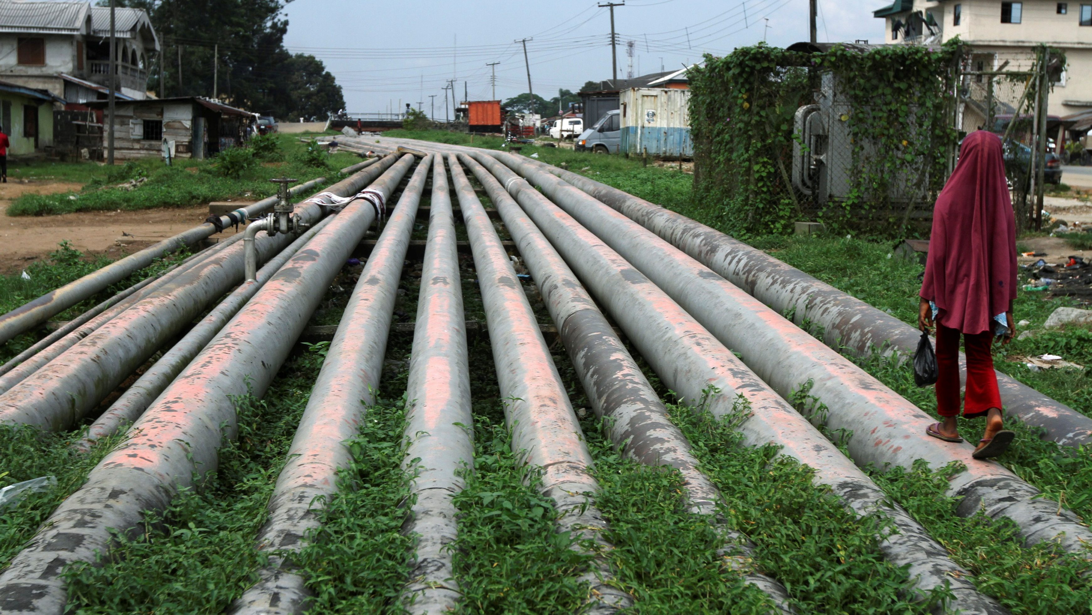 A girl walks on a gas pipeline running through Okrika community near Nigeria's oil hub city of Port Harcourt December 4, 2012.  REUTERS/Akintunde Akinleye/File Photo - RTX2CKKY
