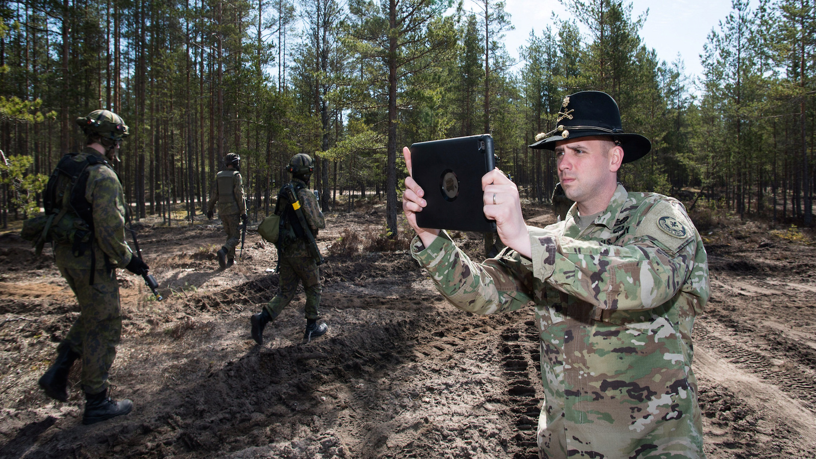 "US Army Cavalry Major Neil Penttila films the action of Finnish troops with a tablet during ""Arrow 16"" mechanised exercise of the Finnish Army in collaboration with US Army Europe's 2nd Cavalry Regiment's Mechanized Infantry Company in Niinisalo, Finland, May 4, 2016."