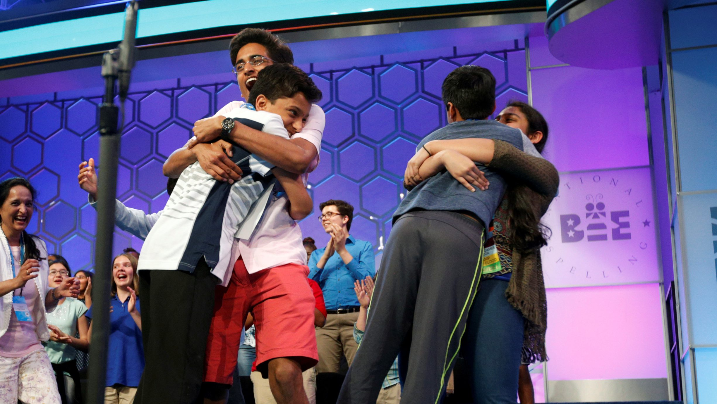 Co-champions Nihar Saireddy Janga (2nd R) and Jairam Jagadeesh Hathwar are swept up into the arms of family members upon completion of the final round of Scripps National Spelling Bee at National Harbor in Maryland, U.S., May 26, 2016. REUTERS/Kevin Lamarque - RTX2EEVE