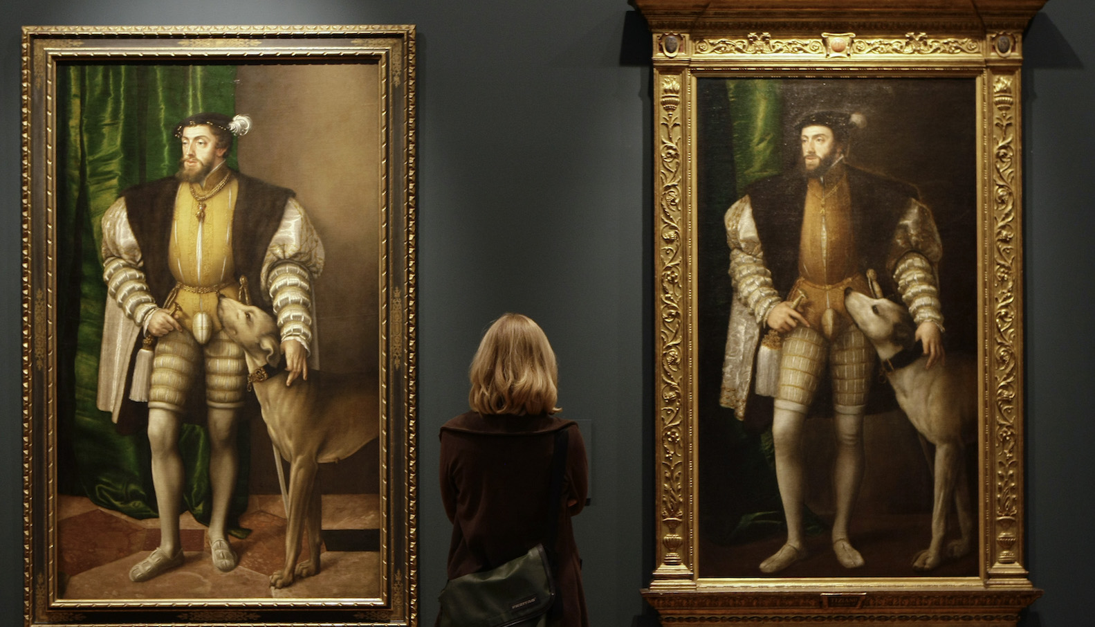 """A woman looks at paintings titled """"Carlos V con un perro"""" by Austrian artist Jacob Seisenegger during the press presentation of the """"The Renaissance Portrait"""" exhibition at Madrid's El Prado museum May 30, 2008. REUTERS/Juan Medina (SPAIN) - RTX6BST"""
