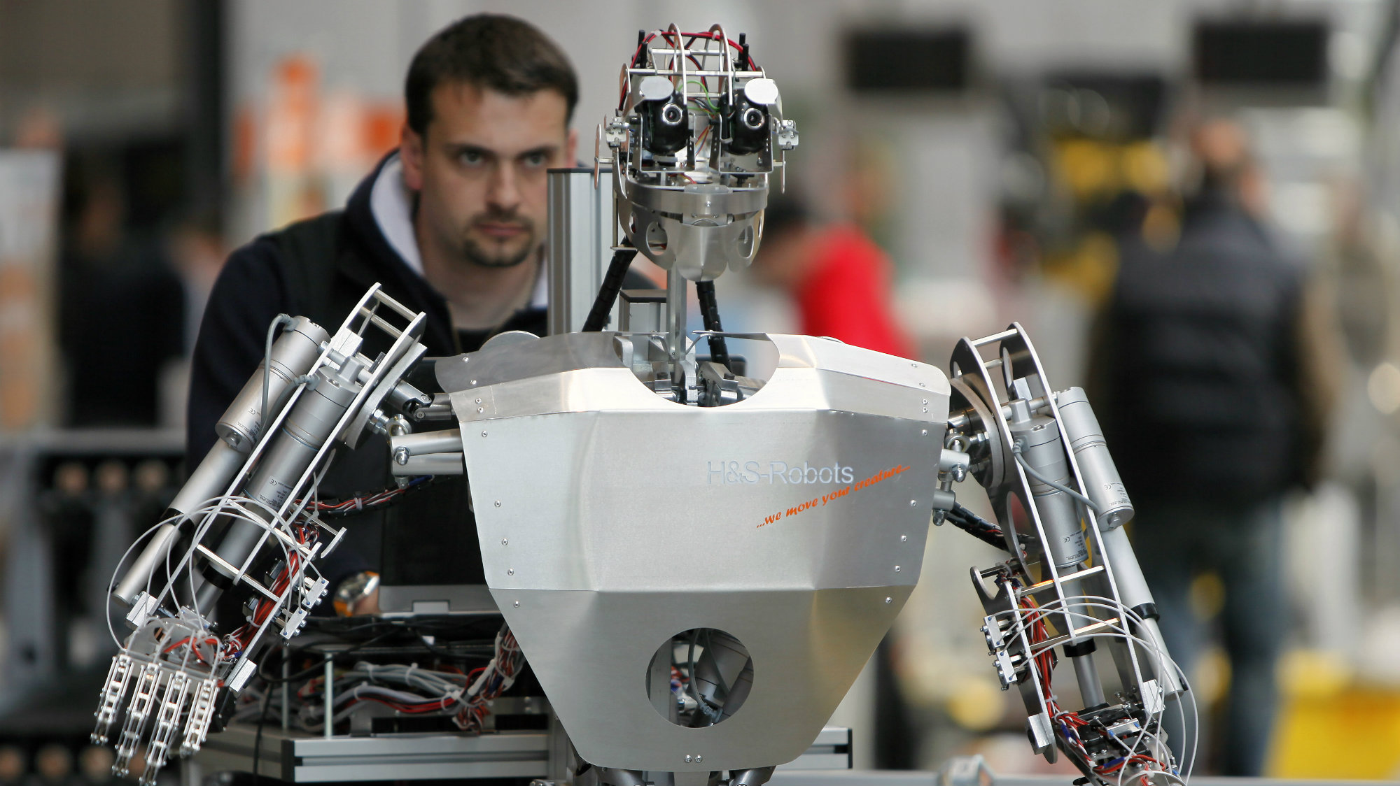 "A worker sets up a robot during final preparations at the ""Hannover Messe"" industrial trade fair in Hanover"