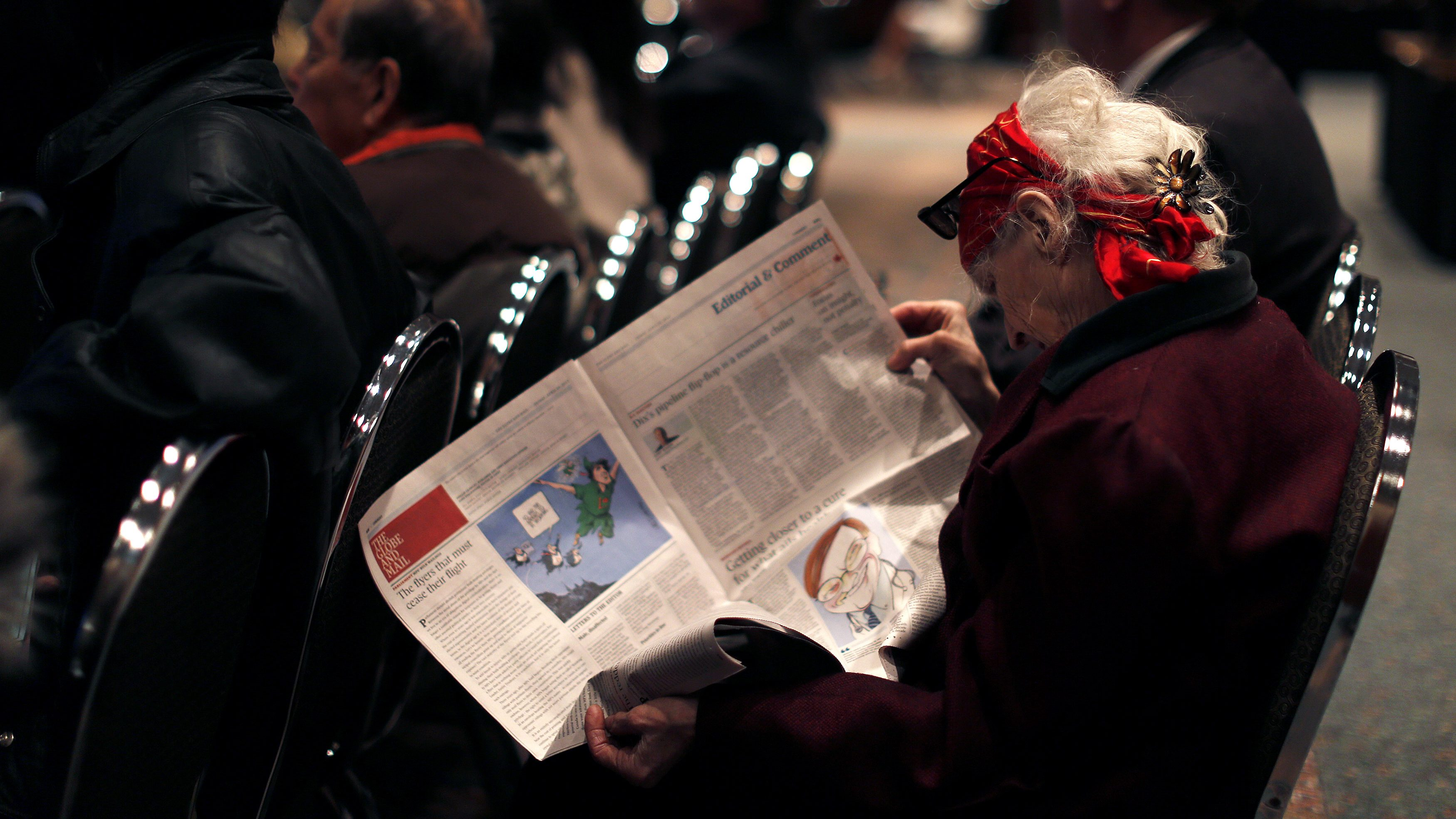 A woman reads The Globe and Mail newspaper at the TransCanada annual general meeting in Calgary