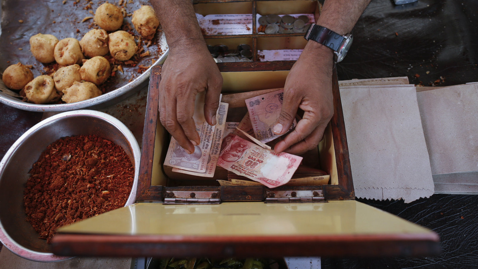 A streetside restaurant owner keeps money received from a customer in Mumbai December 5, 2013. The Indian rupee rose to a five-week high against the dollar and stocks jumped more than 2 percent to near record highs on Thursday as exit polls predicted a strong showing for the key opposition party in recent state elections.