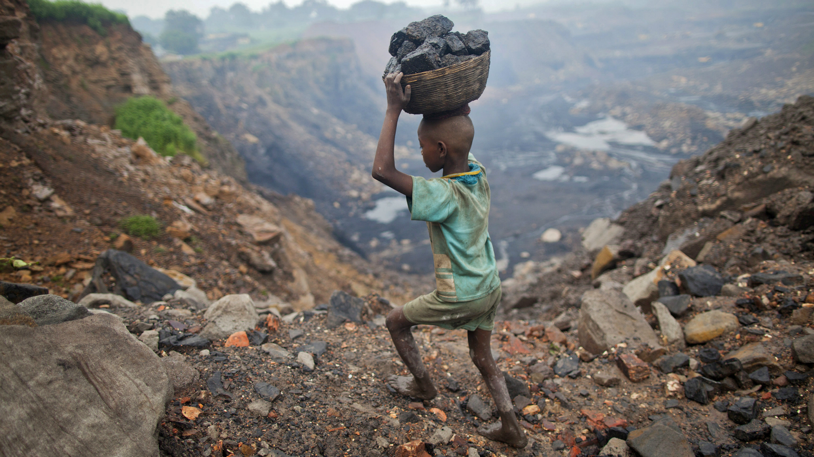 A boy carries coal at an open cast coal field at Dhanbad district in the eastern Indian state of Jharkhand September 20, 2012. With oil and gas output disappointing and hydropower at full throttle, Asia's third-largest economy still relies on coal for most of its vast energy needs. About 75 percent of India's coal demand is met by domestic production and, according to government plans, that won't change over the next five years. Picture taken September 20, 2012. To match INDIA-COAL/