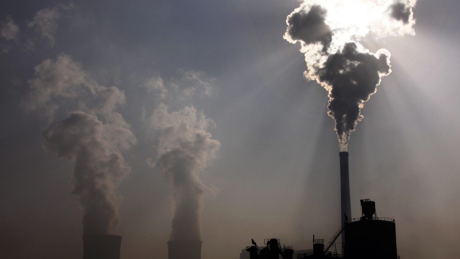 A coal-burning power plant can be seen behind a factory