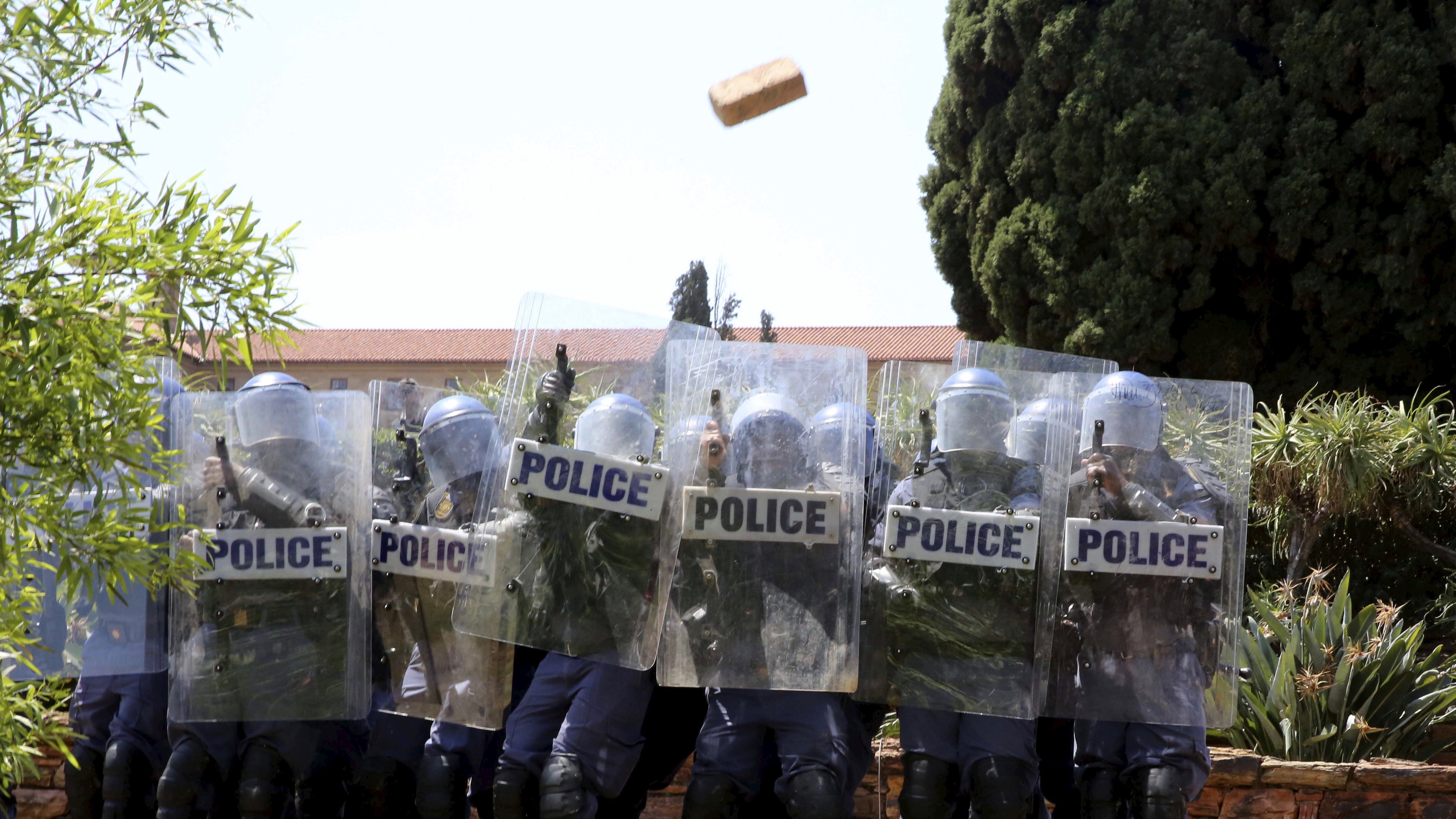 Police duck bricks thrown during a protest by students over planned increases in tuition fees at the Union Buildings in Pretoria, October 23,  2015.