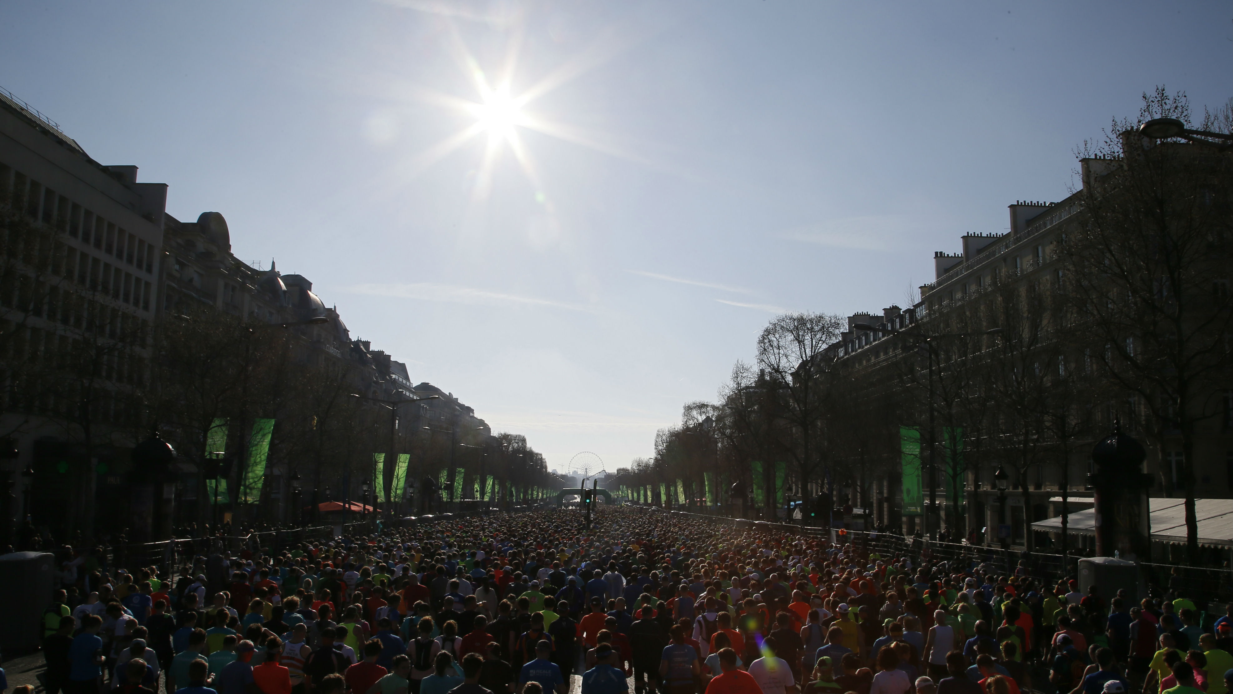 Competitors are seen in silhouette as they run on the Champs Elysees at the start of the 40th Paris Marathon, in Paris, France, April 3, 2016.
