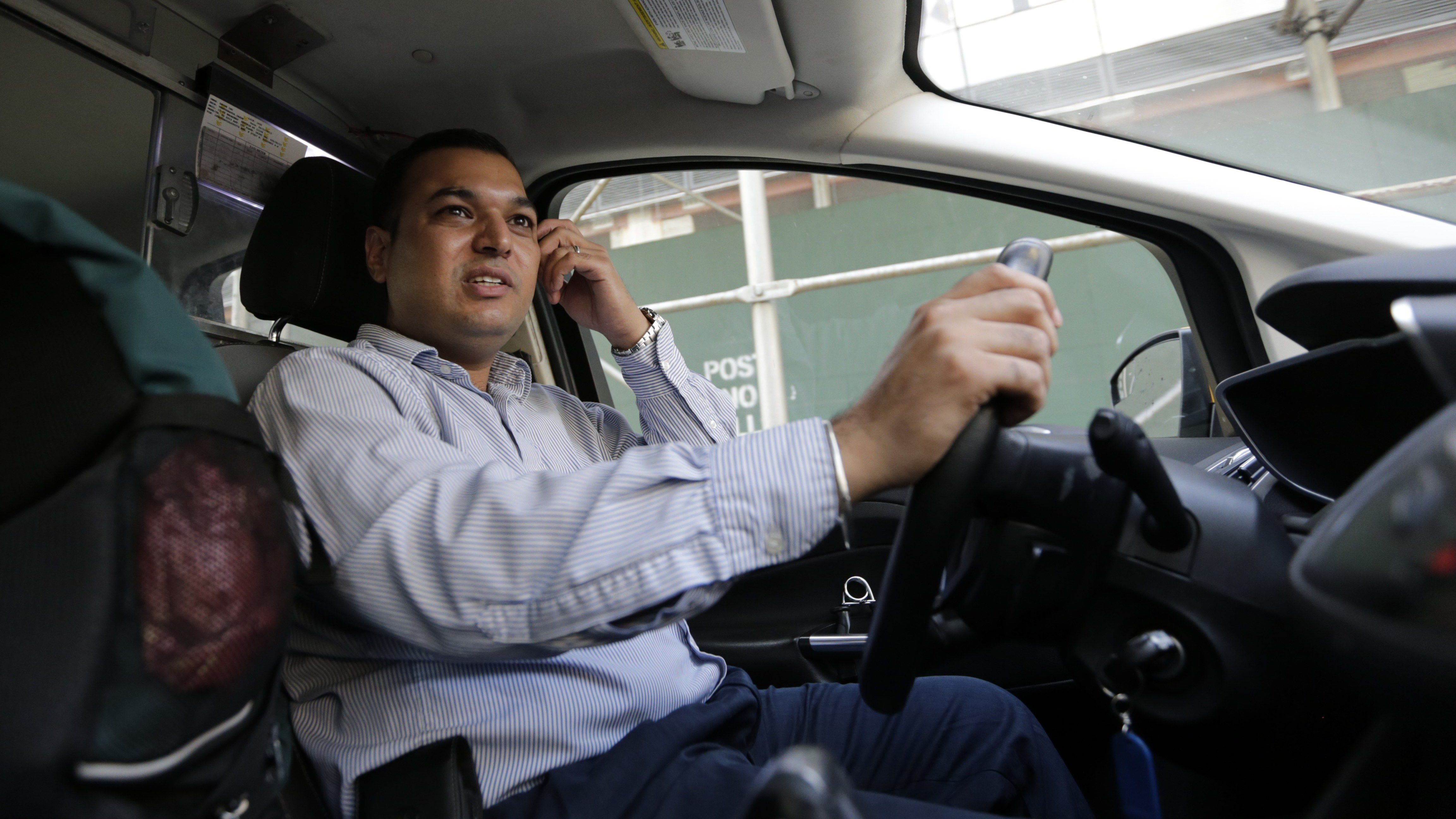 In this July 21, 2015 photo, yellow cab driver Jatinder Singh drives his taxi in New York. Singh owned a yellow cab, which he decided to paint black so he could start driving with Uber. He lasted about six months before he sold the car and returned to taxi driving. (AP Photo/Frank Franklin II)