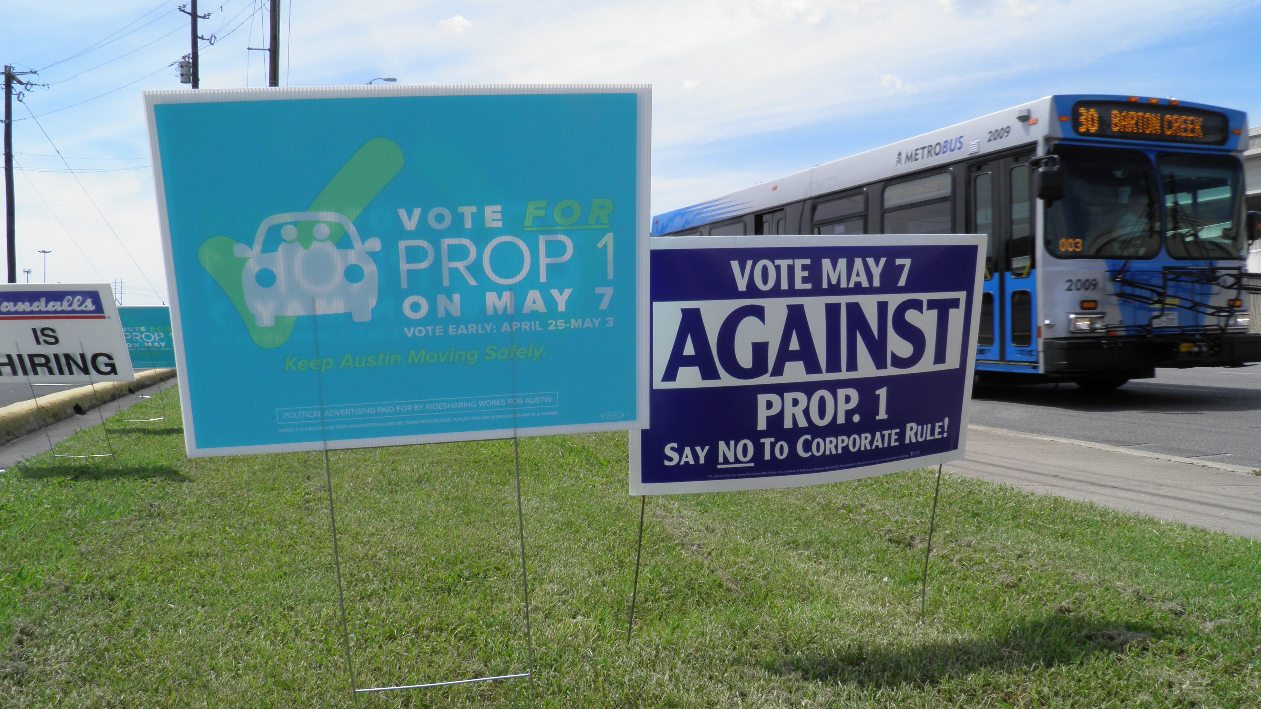 Campaign signs concerning a municipal vote over fingerprint requirements for ride-hailing companies such as Uber and Lyft are seen along a roadway in Austin, Texas, May 6, 2016. REUTERS/Jon Herskovitz - RTX2D5BA