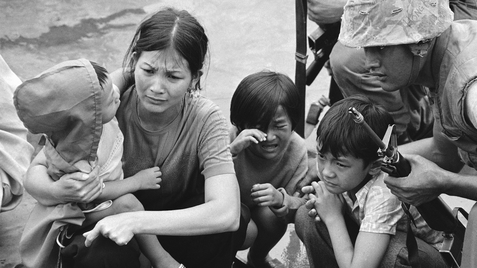 A South Vietnamese mother and her three children stand on the deck of an amphibious command ship being plucked out of Saigon by US Marine helicopters in Vietnam.