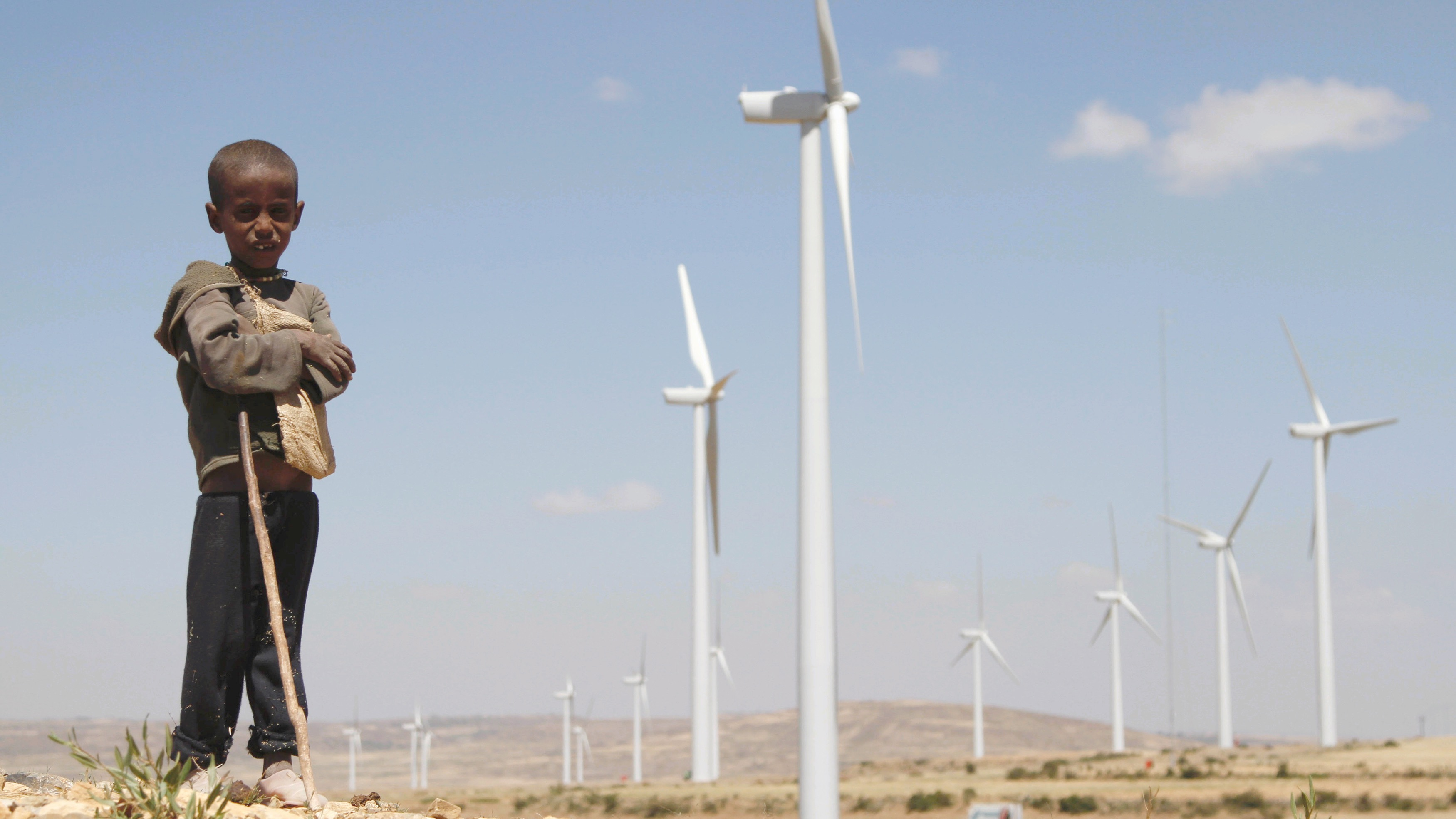 A boy stands in front of wind turbines at the Ashegoda Wind Farm, near a village in Mekelle, Tigray, 780 km (485 miles) north of Addis Ababa October 25, 2013. Africa's biggest wind farm began production in Ethiopia on Saturday, aiding efforts to diversify electricity generation from hydropower plants and help the country become a major regional exporter of energy. Picture taken October 25, 2013. REUTERS/Kumerra Gemechu (ETHIOPIA - Tags: ENERGY BUSINESS ENVIRONMENT TPX IMAGES OF THE DAY) - RTX14PA1