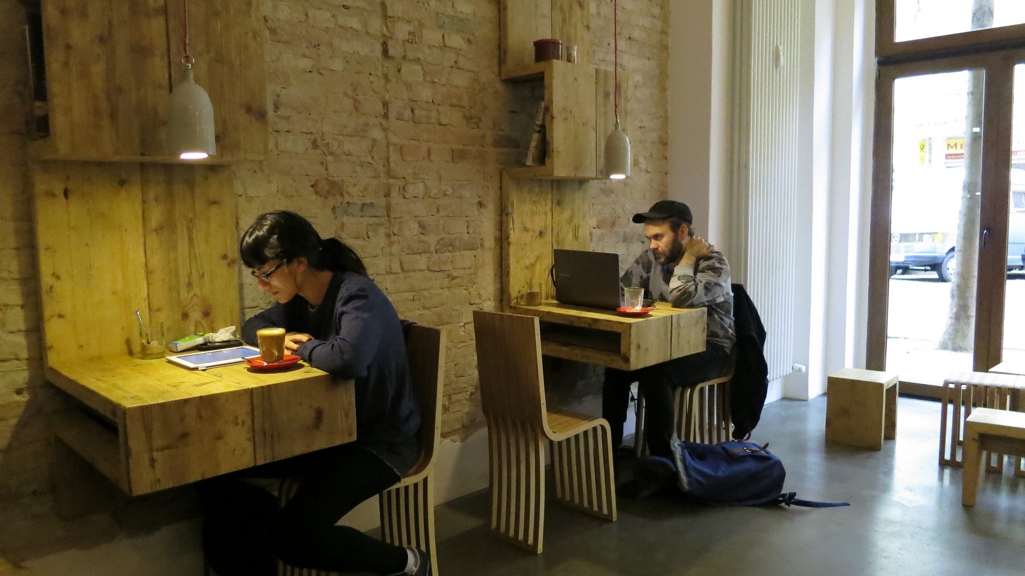 People working on laptops in a cafe.