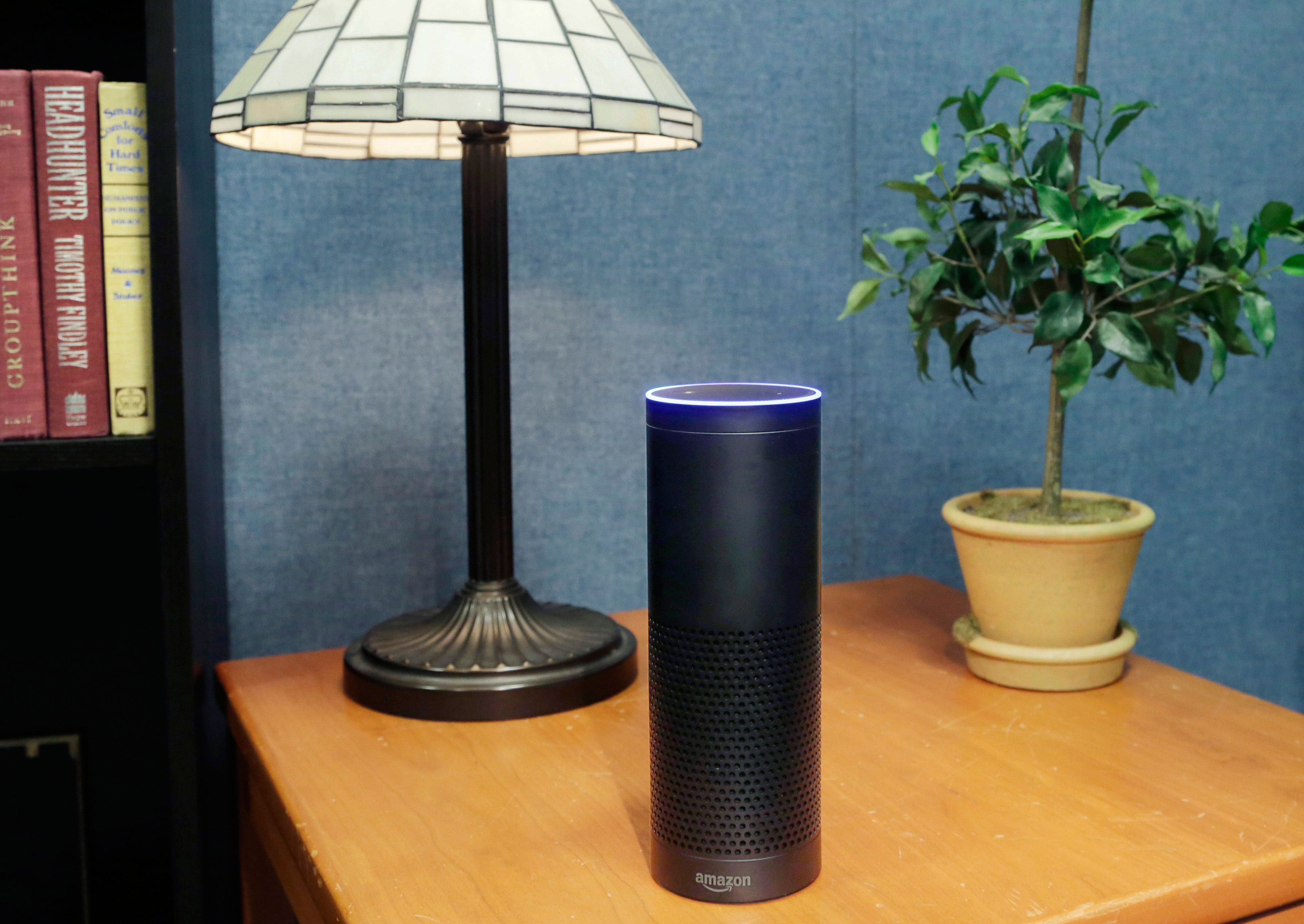 """FILE - This July 29, 2015 file photo made in New York shows Amazon's Echo, a digital assistant that continually listens for commands such as for a song, a sports score or the weather. The company says Echo transmits nothing to Amazon's data centers until you first say """"Alexa"""" or press a button. A blue light also comes on to let you know it's active. (AP Photo/Mark Lennihan, File)"""