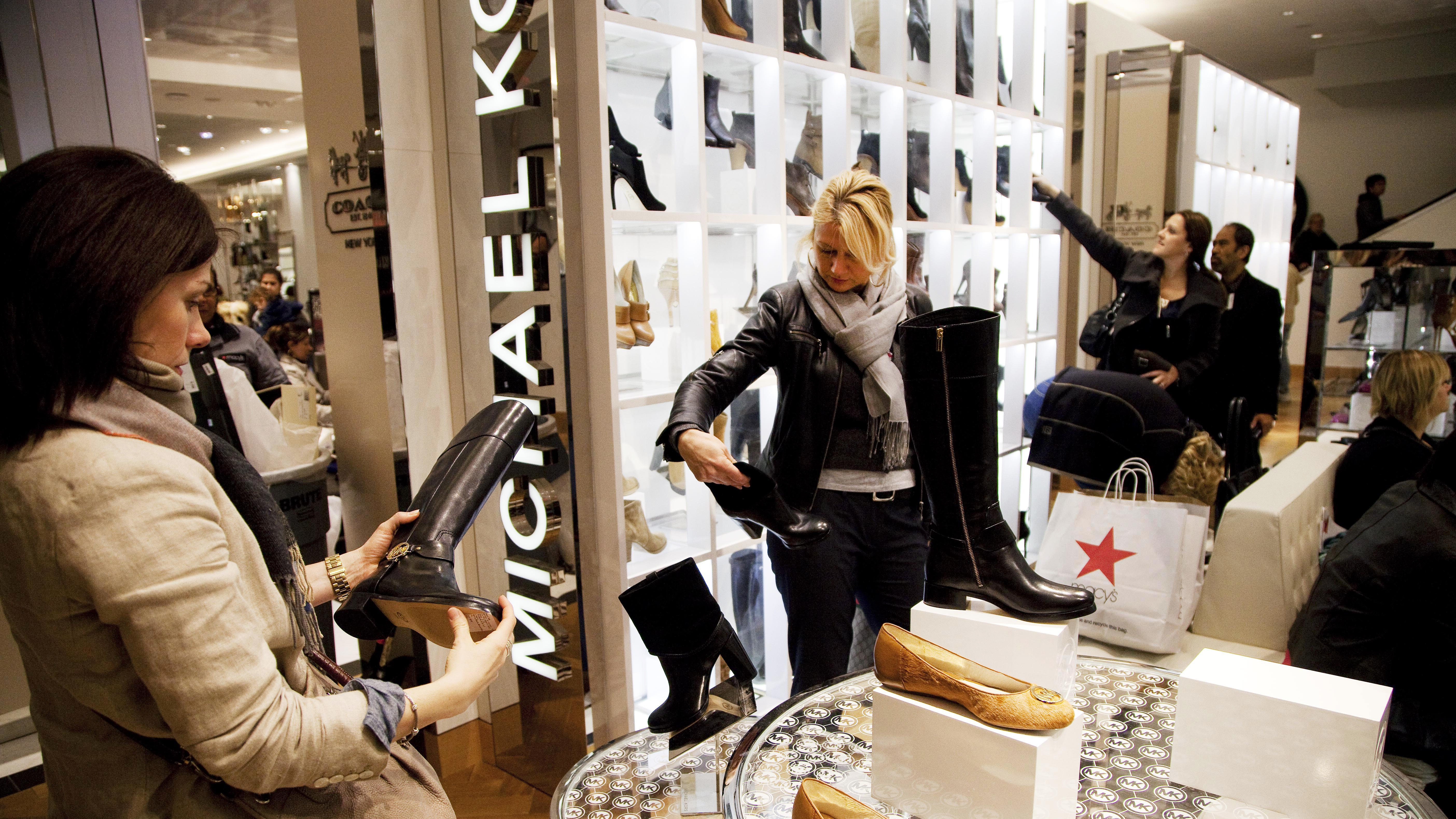 In this Oct. 12, 2012 file photo, women shop in the Michael Kors section of Macy's shoe department in New York.