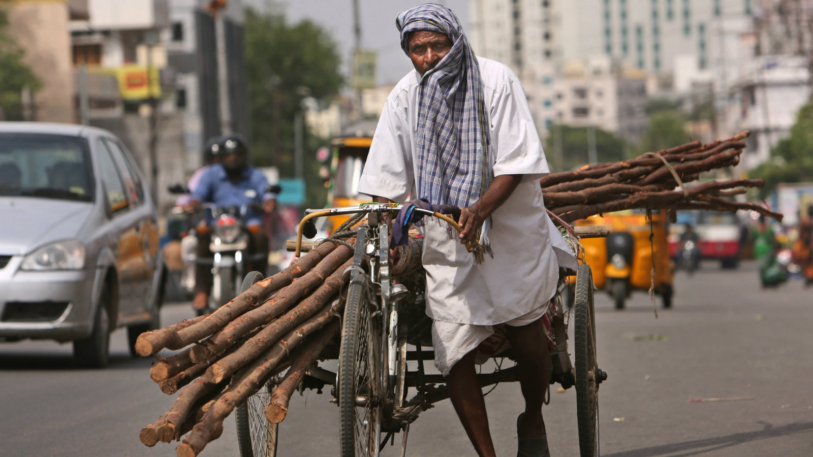 A laborer covers himself with a cloth to protect from the sun as he pulls a rickshaw carrying wooden logs on a hot summer afternoon in Hyderabad, India, Friday, May 20, 2016. The prolonged heat wave this year has already killed hundreds and destroyed crops in more than 13 states. The extreme heat has impacted hundreds of millions in western India with record temperatures Friday reaching as high as a scorching 51 degrees Celsius (123.8 Fahrenheit).