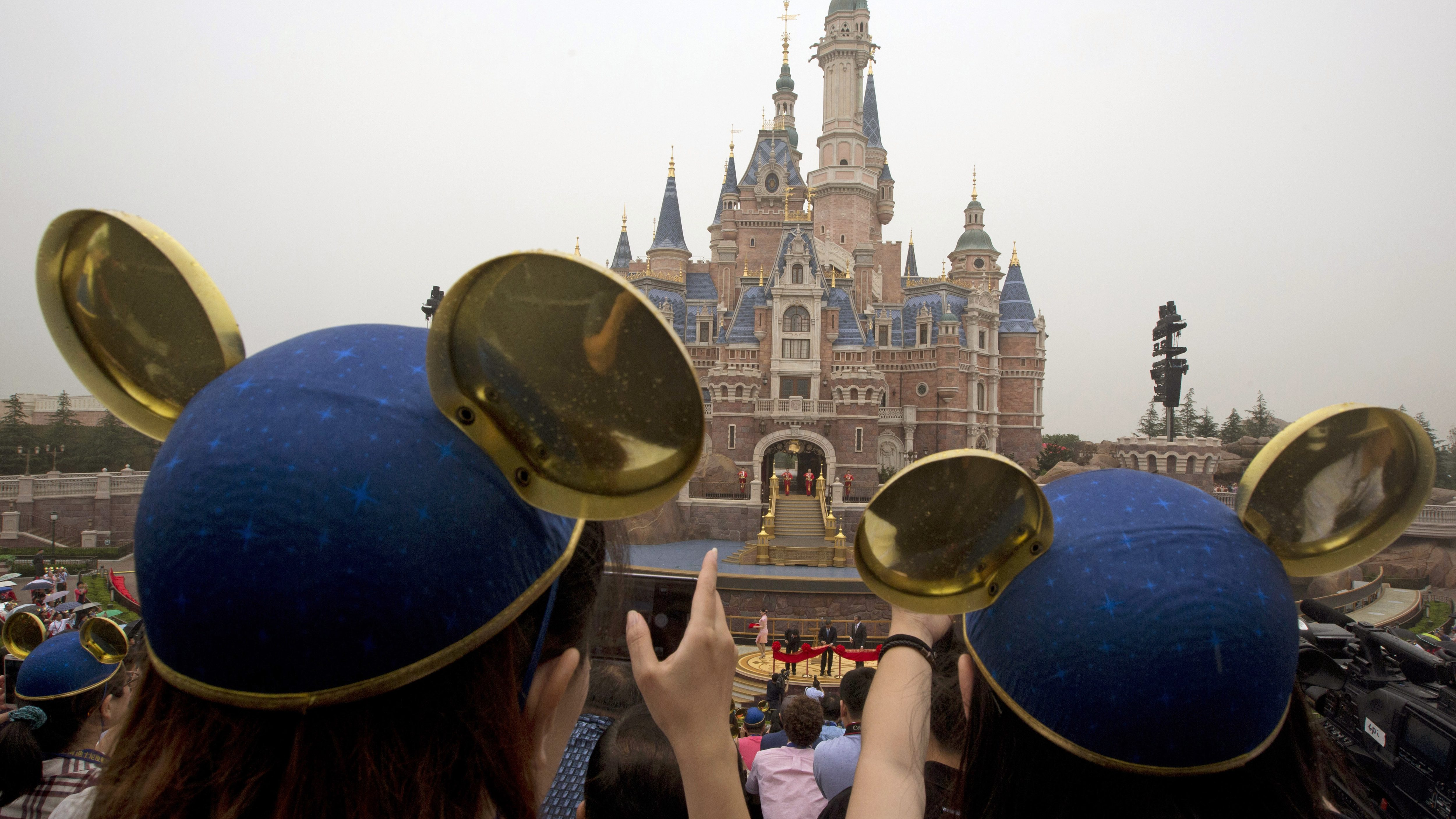 Visitors wearing Mickey hats take photos of Shanghai Mayor Han Zheng, left, Chinese Vice Premier Wang Yang, center, and Disney CEO Bob Iger preparing to cut the red ribbon during the opening ceremony for the Disney Resort in Shanghai, China, Thursday, June 16, 2016. Walt Disney Co. opened its first theme park in mainland China on Thursday at a ceremony that mixed speeches by Communist Party officials, a Chinese children's choir and actors dressed as Sleeping Beauty and other Disney characters. (AP Photo/Ng Han Guan)