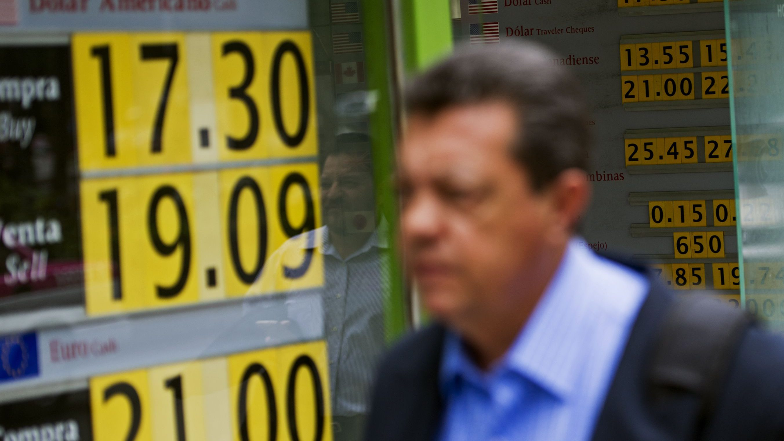 A pedestrian walks past a currency exchange store in Mexico City, Friday, June 24, 2016. The Mexican peso continues to weaken against international currencies after Britain's vote to exit the European Union. (AP Photo/Nick Wagner)