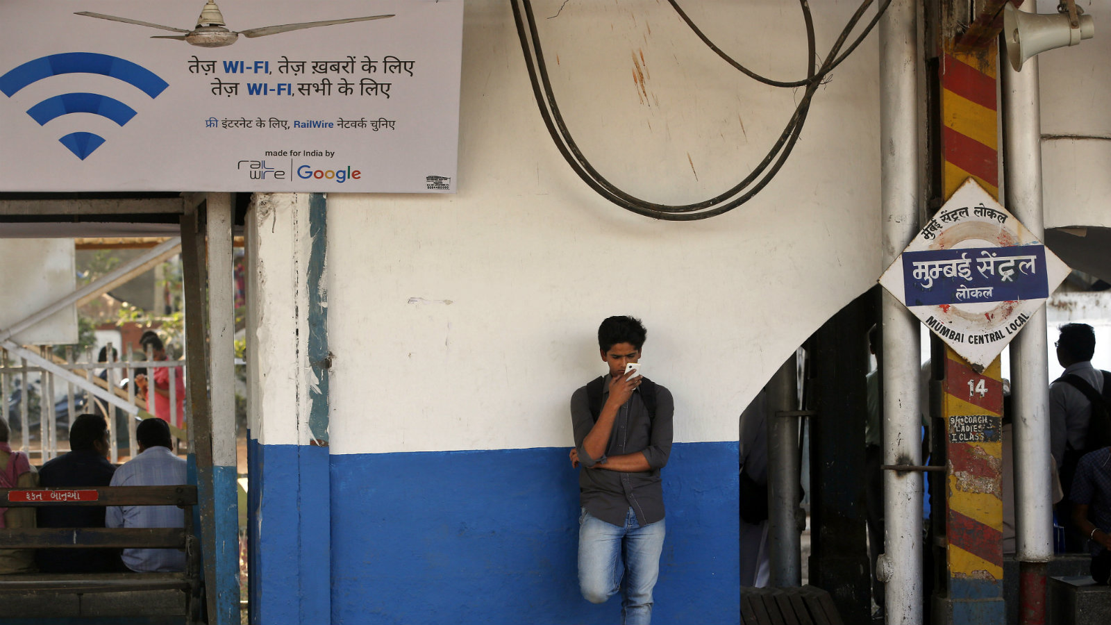 An Indian traveler uses a free WiFi service to browse the net at Mumbai Central Train Station in Mumbai, India, Friday, Jan. 22, 2016. Google Inc. has begun offering free WiFi to Mumbai train passengers in hopes of boosting its role in the Indian market. A poster on the left says 'fast WiFi, for fast news, fast WiFi, for everyone'.