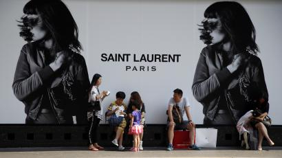 Chinese tourists take a rest during shopping outside a fashion store in Paris, France, Wednesday, Aug. 12, 2015.